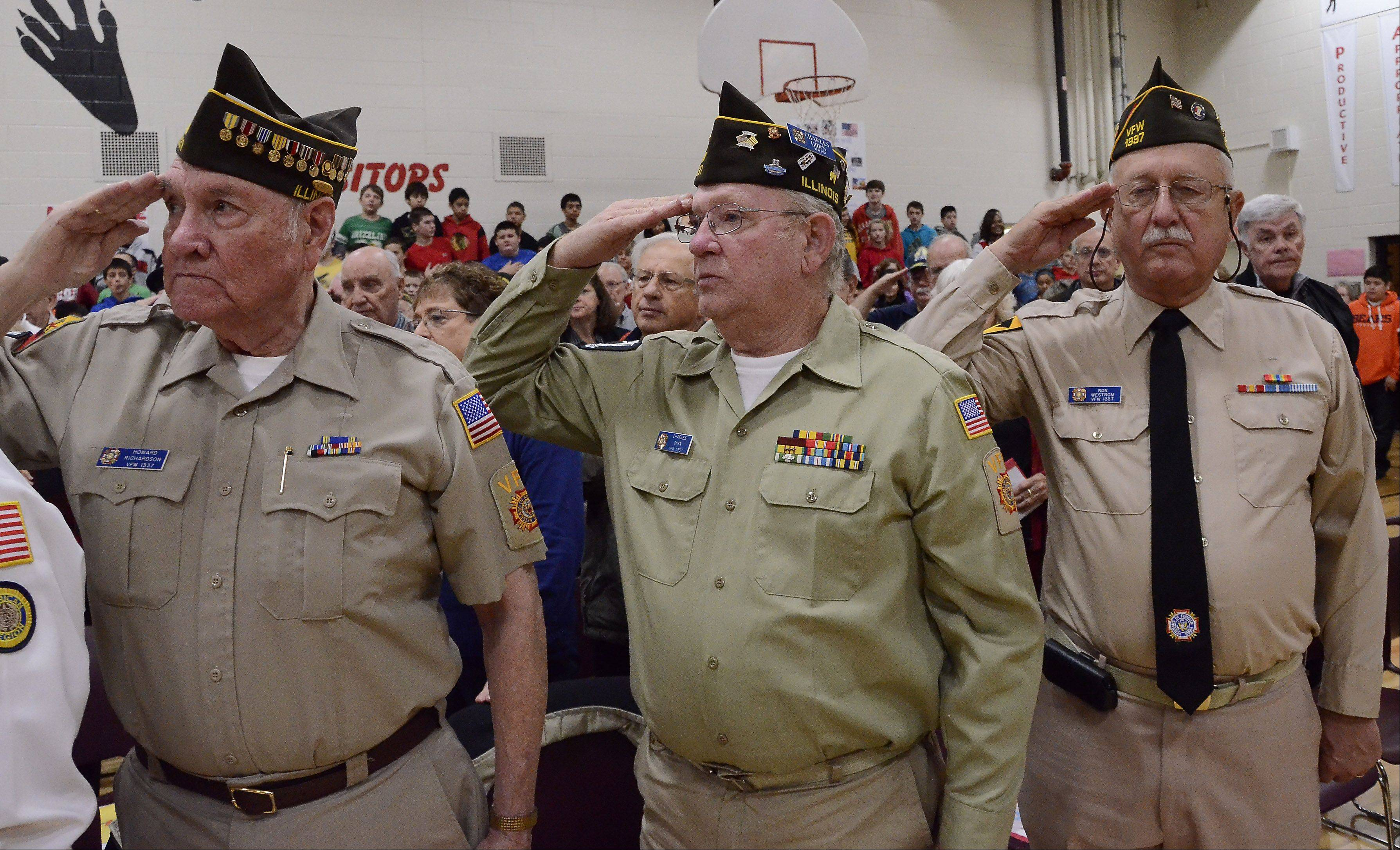 Members of Veterans of Foreign Wars Post 1337 Howard Richardson of Mount Prospect, left, Charles Ohrn of Rolling Meadows and Ron Westrom of Mount Prospect salute the colors at the Veterans Day breakfast and assembly Friday at MacArthur Middle School in Prospect Heights.