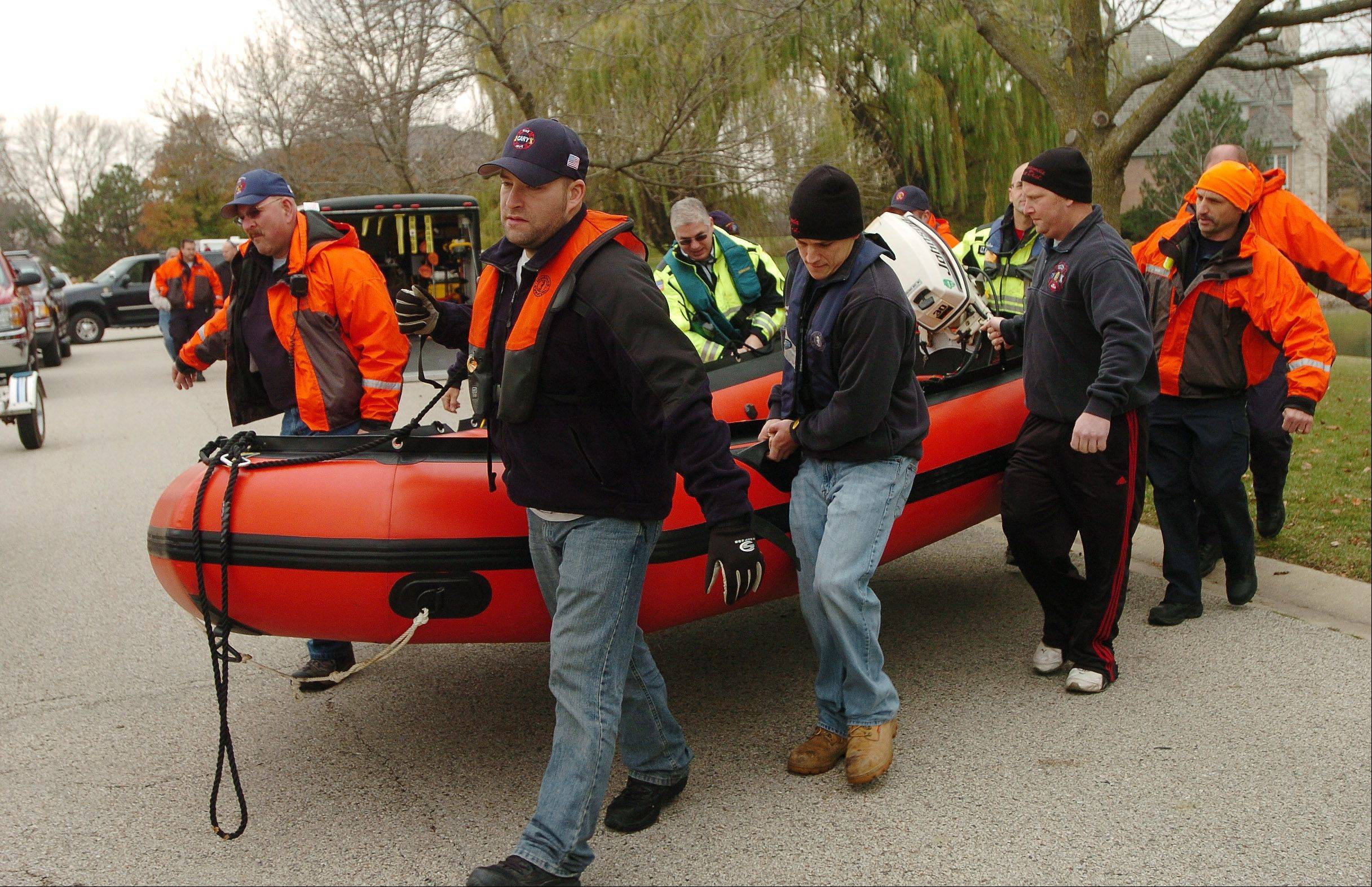 A diving team takes equipment across the road to another pond on Spring Creek Drive in South Barrington, where they eventually retrieved a body.