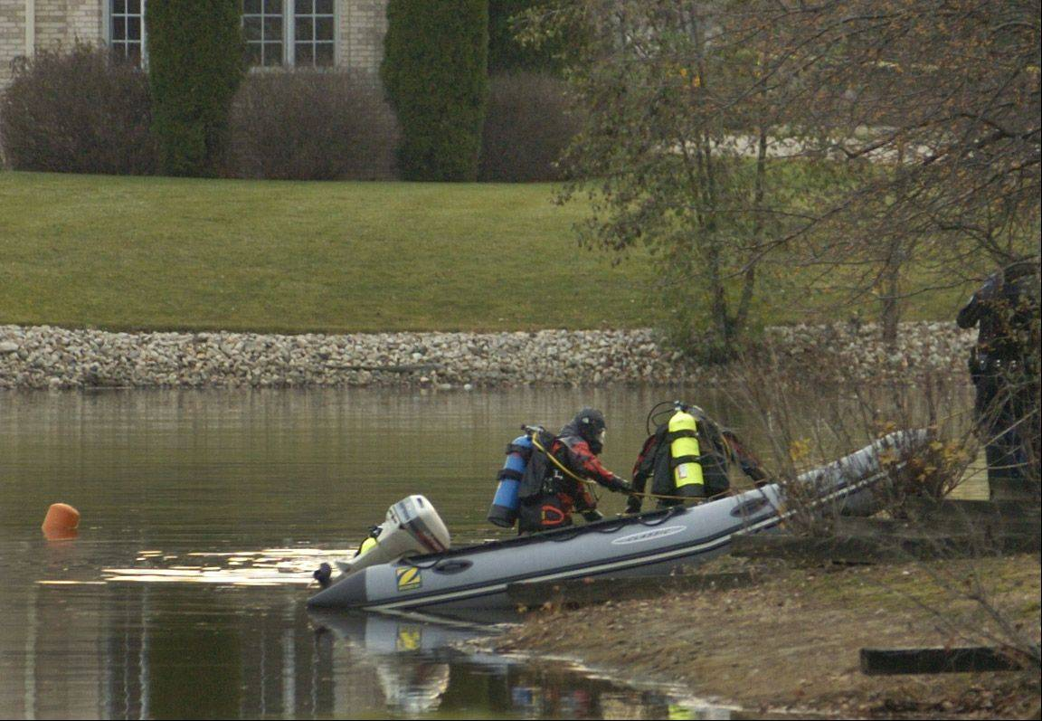 Divers retrieve a body from a pond on Spring Creek Drive in South Barrington.