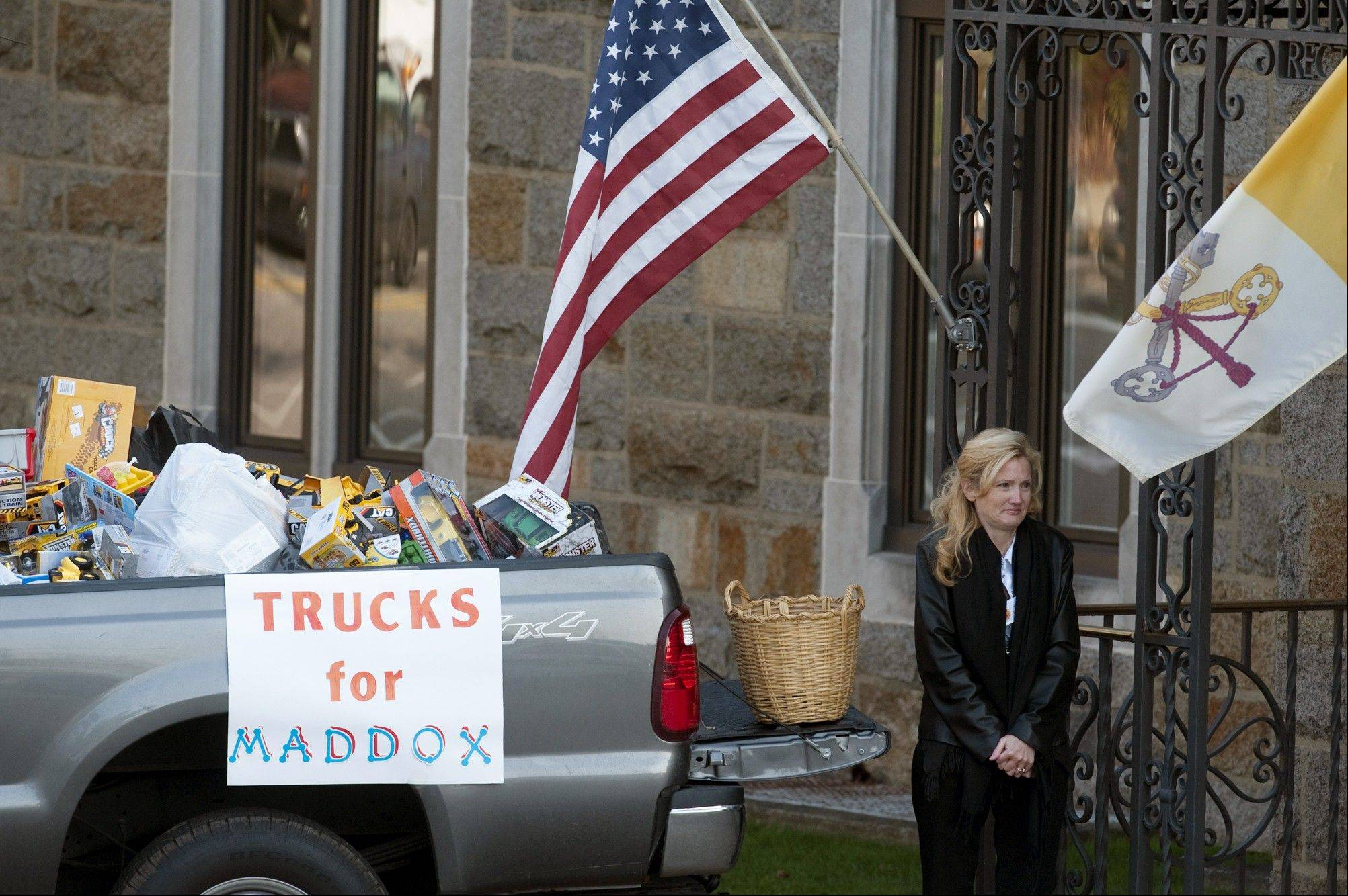 A woman collects toy trucks Friday at the funeral of 2-year-old Maddox Derkosh at Saint Bernard Church in Mount Lebanon, Pa.