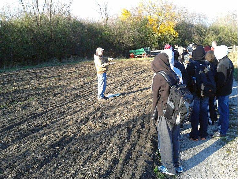 Students walk with David Brooks of Spring Valley Nature Center while he explains the physical environment that German immigrant farmers faced in 1880.