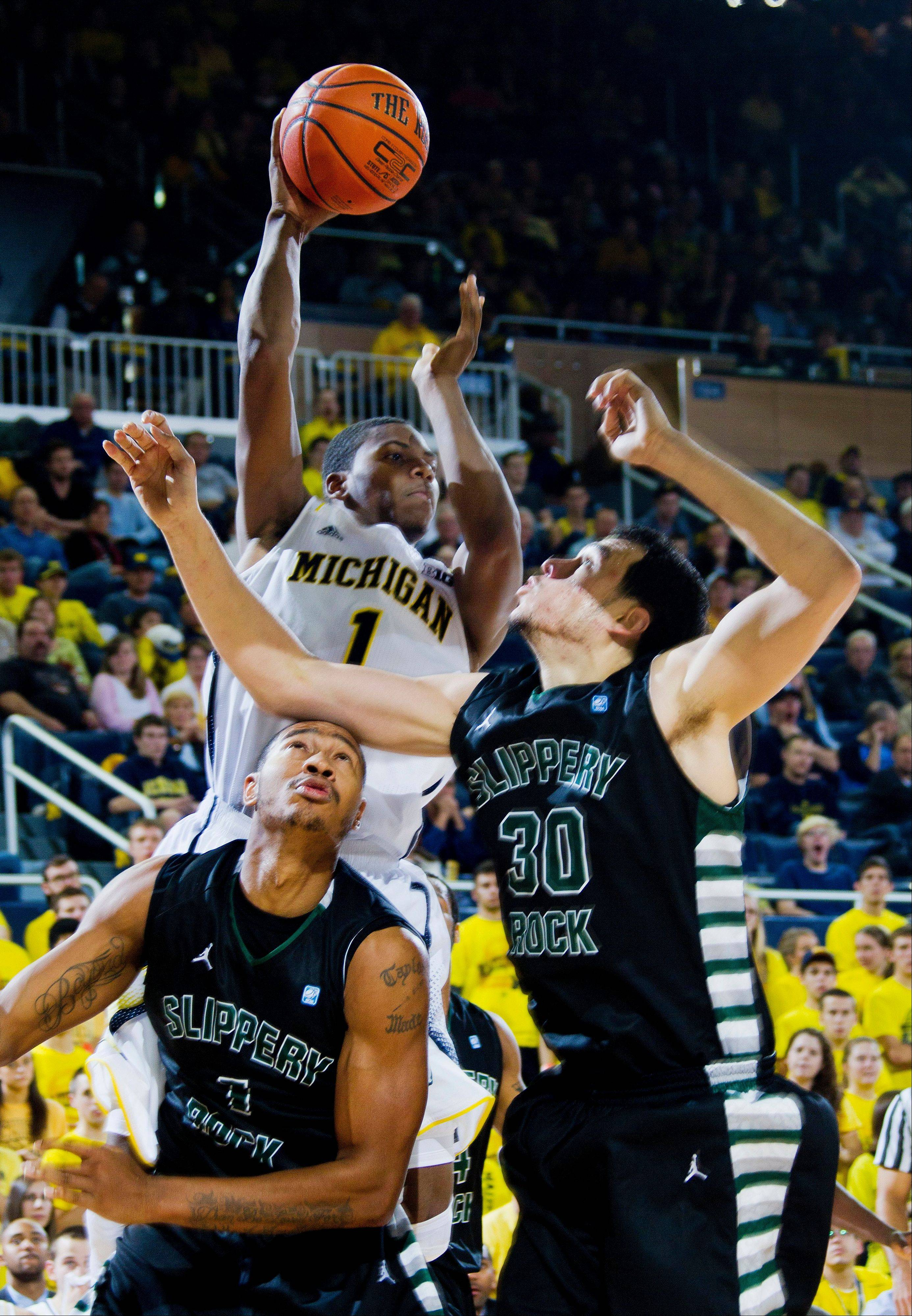 Michigan forward Glenn Robinson III, top, jumps for the ball over Slippery Rock forward Devin Taylor, bottom left, and center Luiz Santos (30) Friday during the second half at Crisler Center in Ann Arbor, Mich.