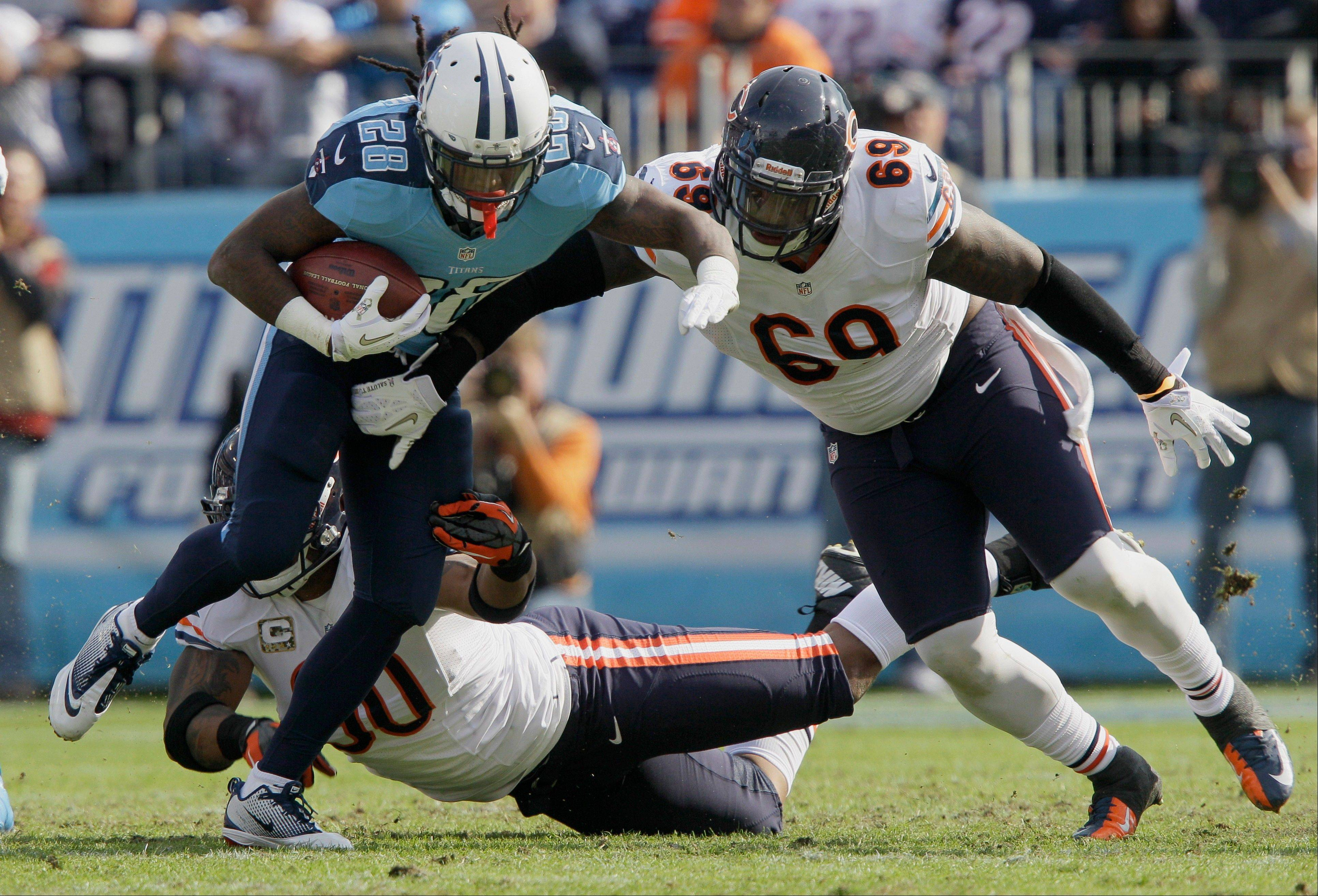 Tennessee Titans running back Chris Johnson is stopped by Bears defensive tackle Henry Melton (69) and veteran DE Julius Peppers Sunday.