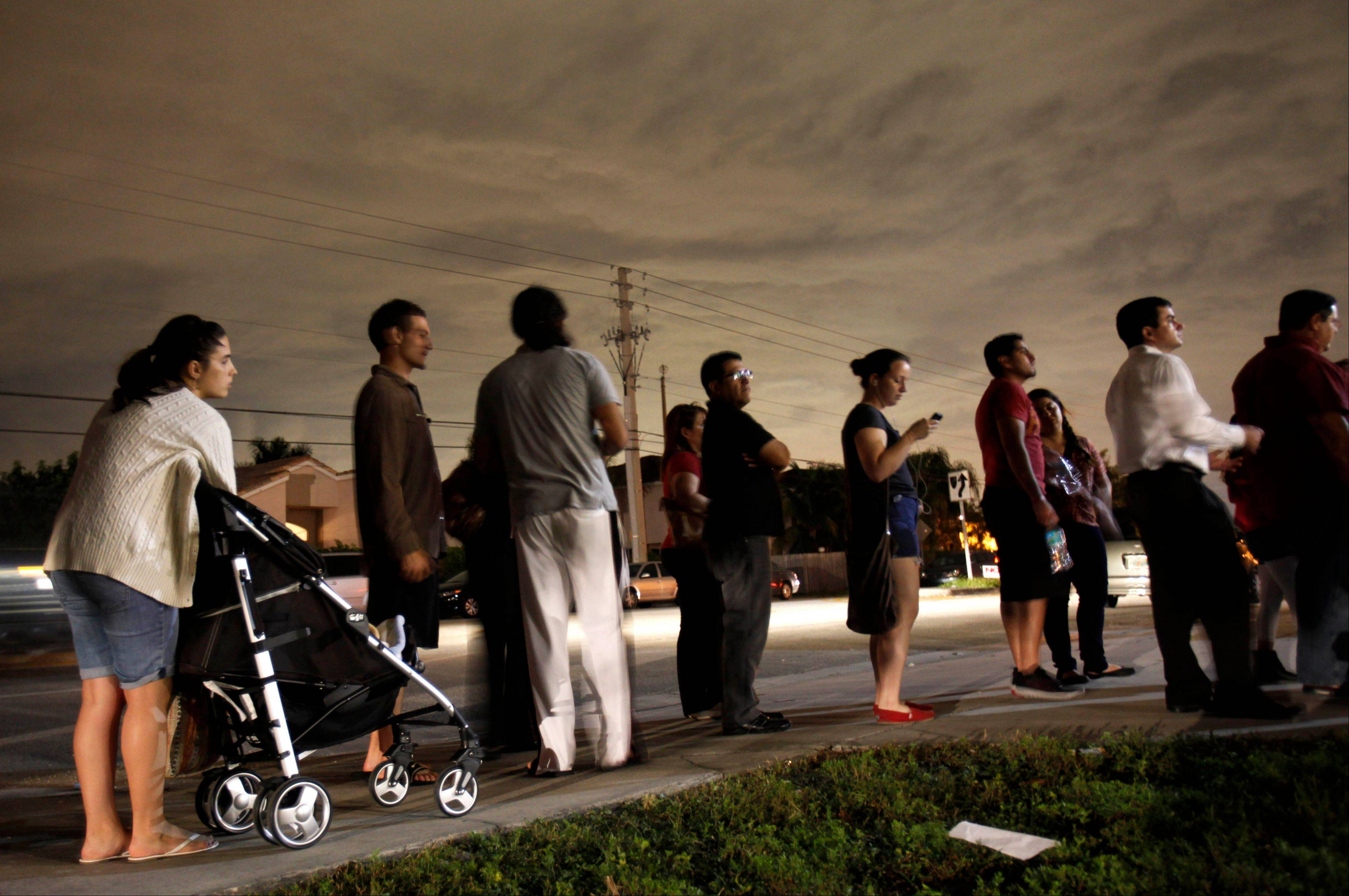Associated Press Voters line up in the dark Tuesday to beat the 7 p.m. deadline to cast their ballots at a polling station in Miami.