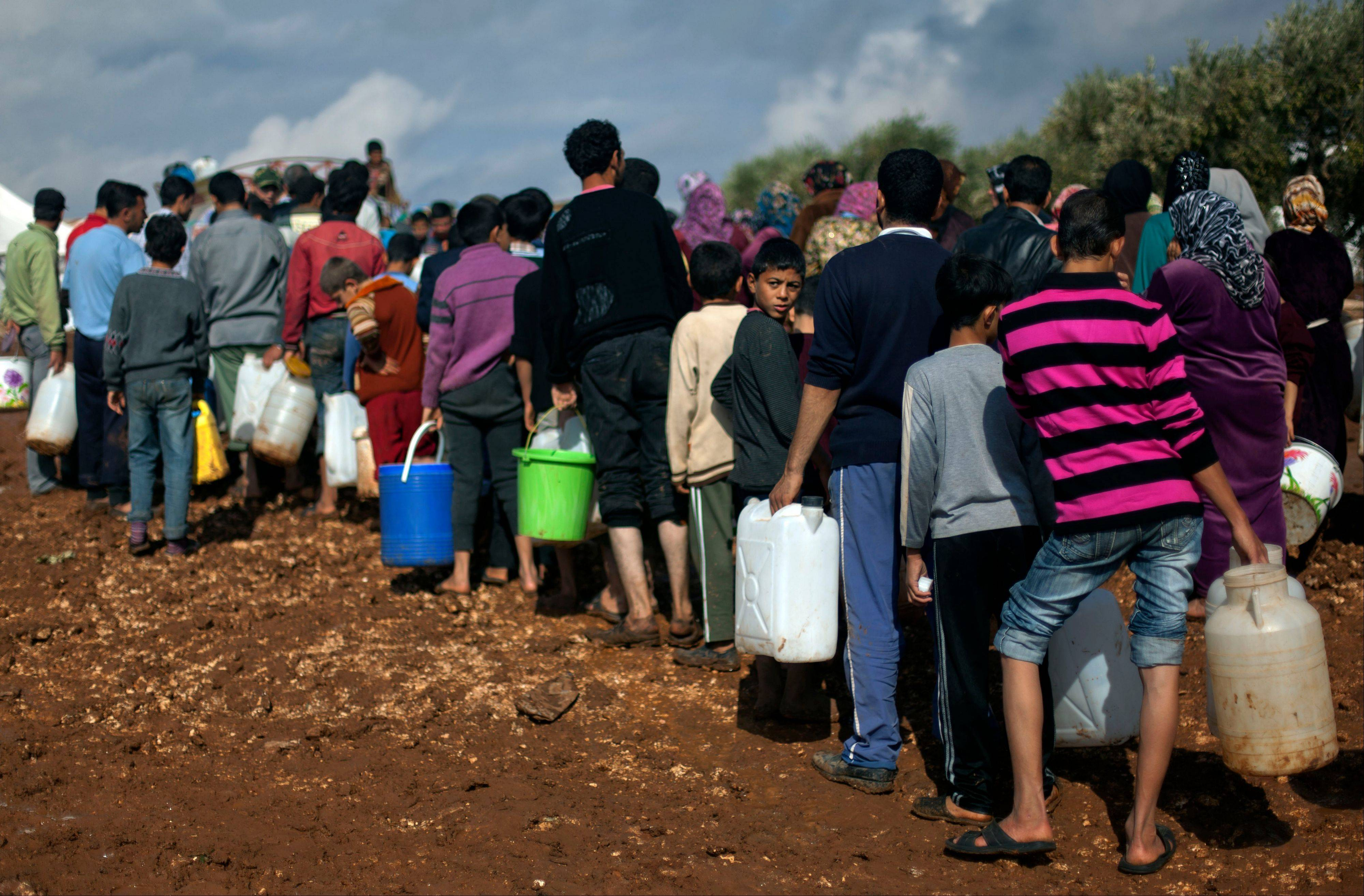 Syrians who fled from the violence in their village, carry plastic containers Saturday as they line up to fill them with water at a displaced camp, in the Syrian village of Atma, near the Turkish border.
