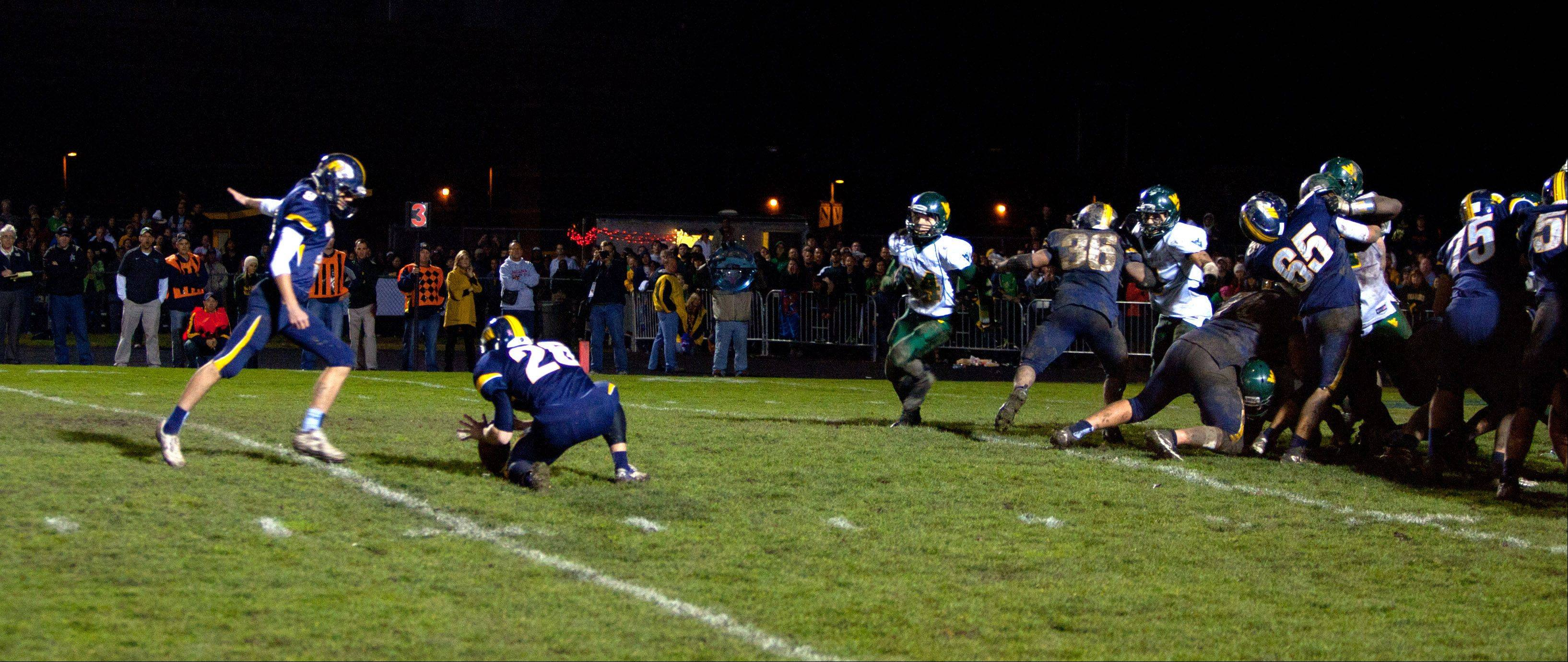 With seconds remaining, and under the hold of Conner Milliren (26), kicker Ryan Mulhern kicks the game winning field goal, for a 23-20 win over Waubonsie Valley.