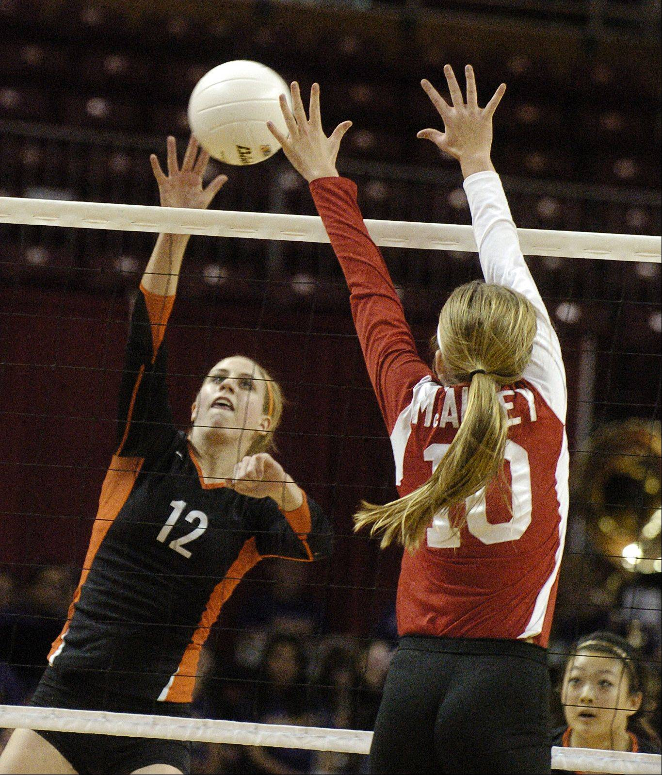 Paul Michna/pmichna@dailyherald.com Jordan Bauer of Libertyville,left hits the ball while Ryann DeJarld of Mother McAuley attempts to block it. This took place during the Libertyville vs. Mother McAuley Class 4A third-place volleyball game at Redbird Arena, on Illinois State campus Saturday.
