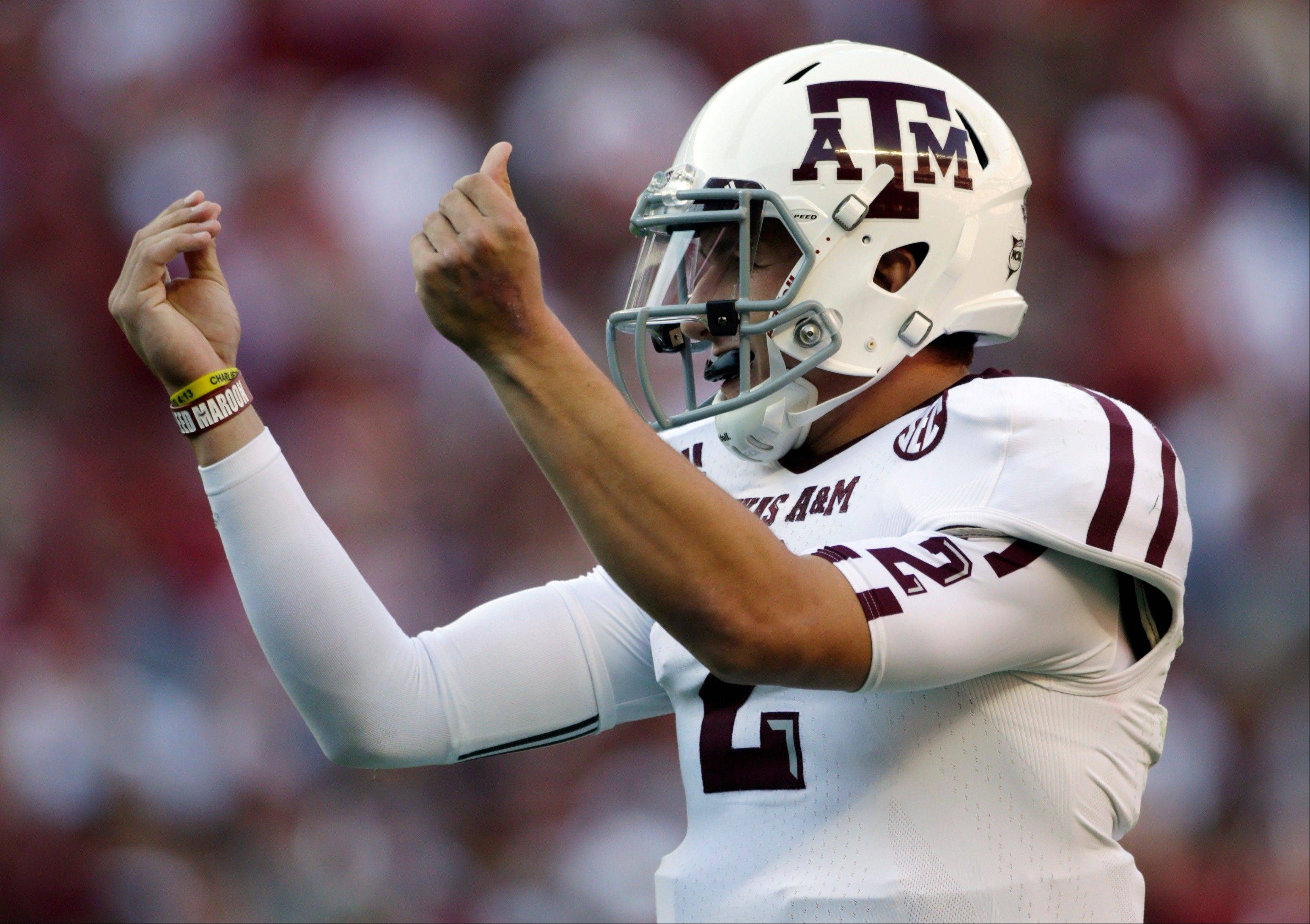 Texas A&M quarterback Johnny Manziel reacts after the Aggies scored their third touchdown of the first quarter against Alabama Saturday at Bryant-Denny Stadium in Tuscaloosa, Ala.