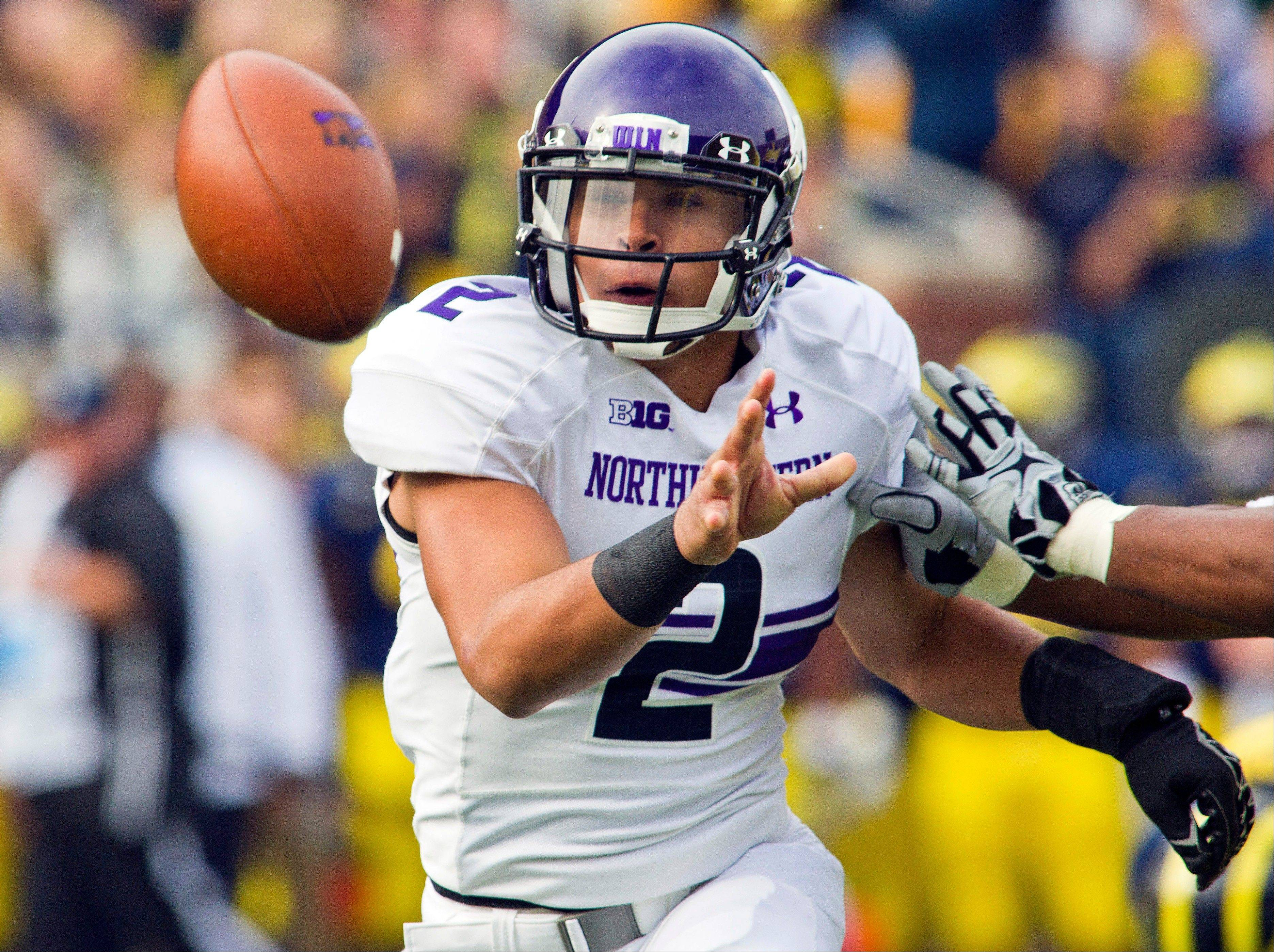 Northwestern quarterback Kain Colter pitches the ball toward a running back Saturday during the first quarter against Michigan in Ann Arbor.