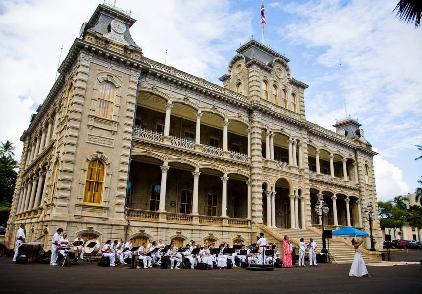 The Royal Hawaiian Band and a hula dancer play in front of Iolani Palace in Honolulu.