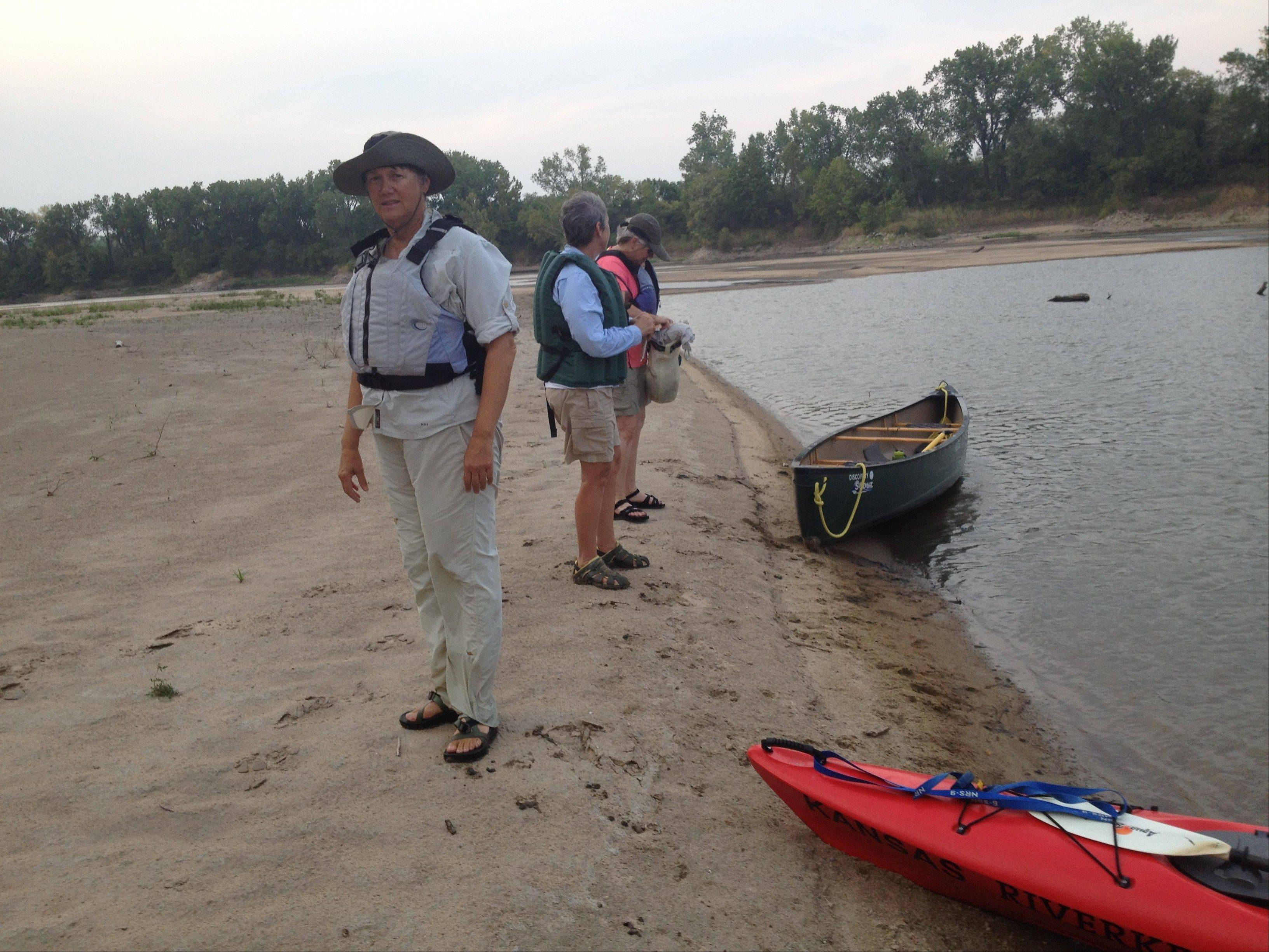 Paddlers take stop on a sandbar along the Kansas River near DeSoto, Kan.