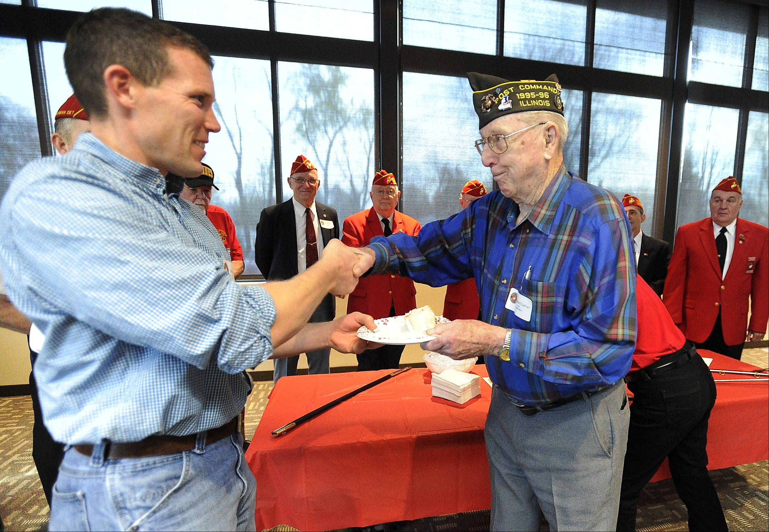 Pfc. Marine Leonard Zaehler, 93, who served in World War II, presents a piece of cake to the youngest Marine, Mike Kubas of Grayslake, who is a 3rd generation Marine at the Veterans Day celebration held Saturday at St. Peter Lutheran Church in Arlington Heights.