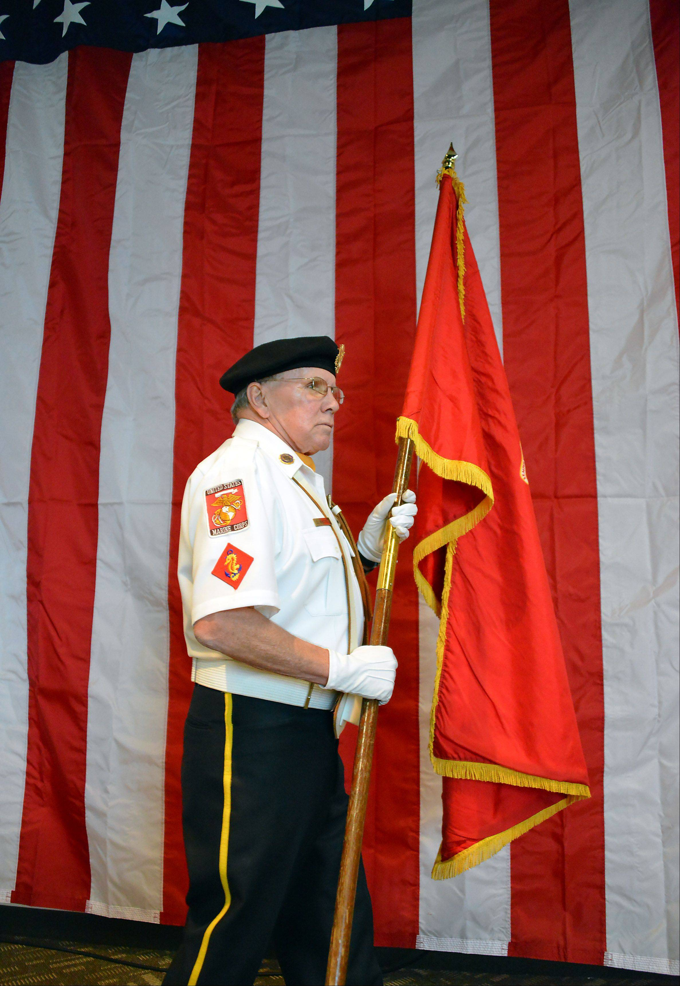 Dick Whitney of Arlington Heights delivers the Marine Corps flag at the Veterans Day celebration held Saturday at St. Peter Lutheran Church in Arlington Heights. The Northwest Suburban Marine Corps League was celebrating the 237th birthday of the U.S. Marine Corps.