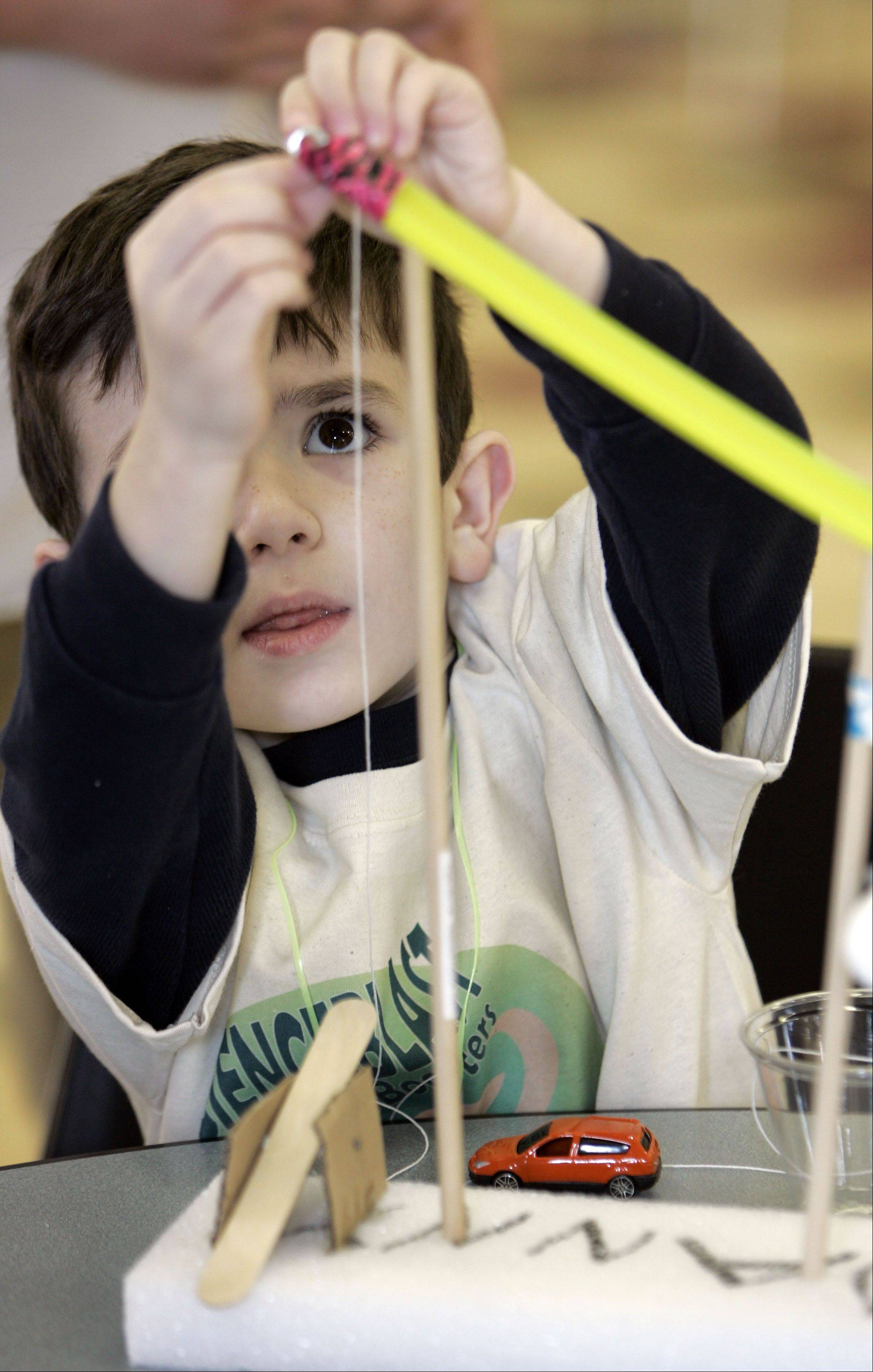"Six-year-old Danny Brankin of Batavia attaches some string to his project during ""ScienceBlast"" hosted by Batavia High School Saturday."