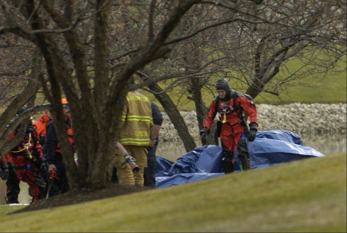 Divers on Friday retrieve the body of 25-year-old Vance Nwankwo from a pond on Spring Creek Drive in South Barrington.