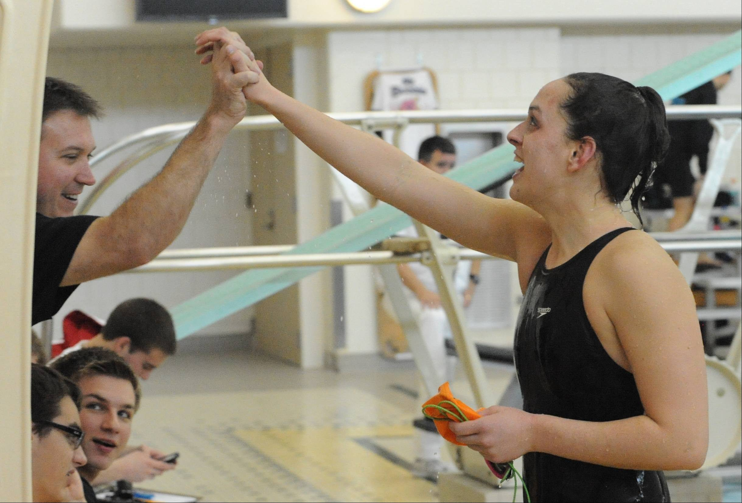 Hersey senior Amanda Petro, right, high-fives coach Dick Mortensen following her winning effort in the 200-yard IM at Saturday's Stevenson sectional meet.