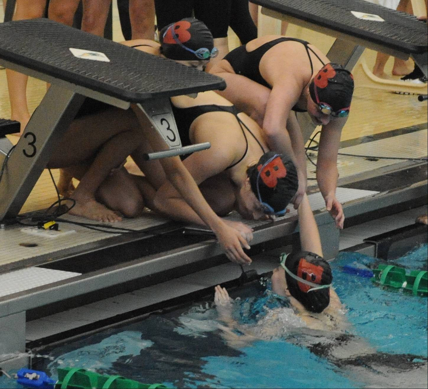 Barrington's 200-yard freestyle relay members congratulate teammate Kirsten Jacobsen after her winning anchor leg in the Stevenson sectional Saturday.