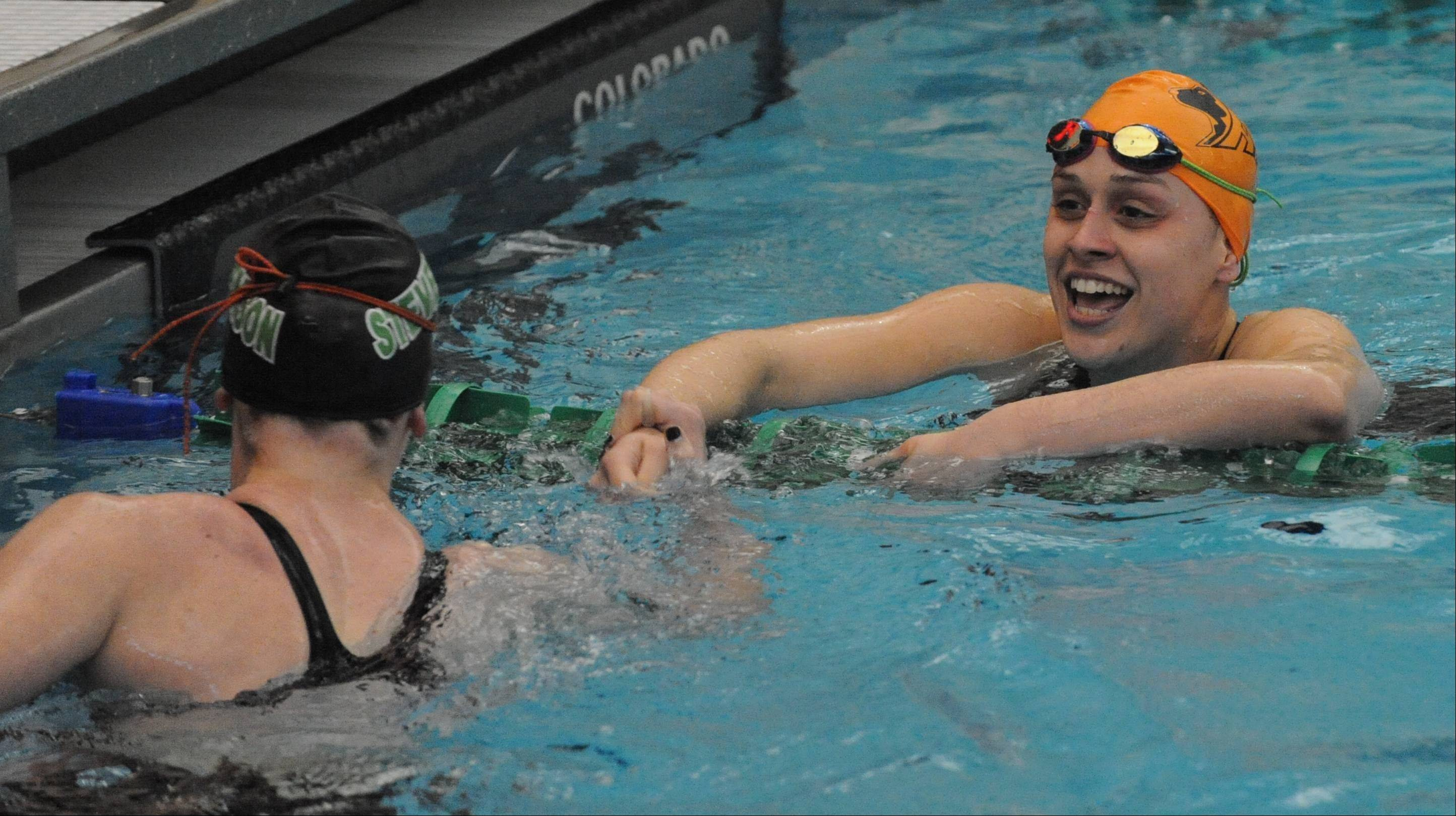 Hersey's Amanda Petro, facing, and Stevenson's Madison Blaydes like their state-qualifying results in the 100-yard backstroke.