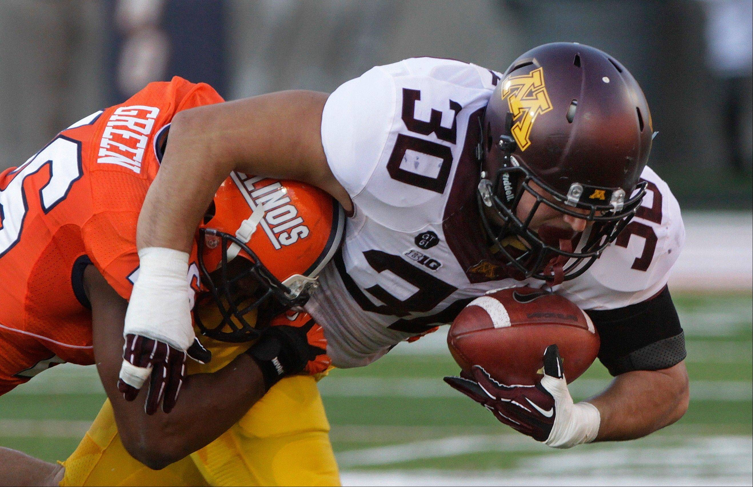 Minnesota fullback Mike Henry holds on to the ball near Illinois defensive back Justin Green Saturday during the first half in Champaign.