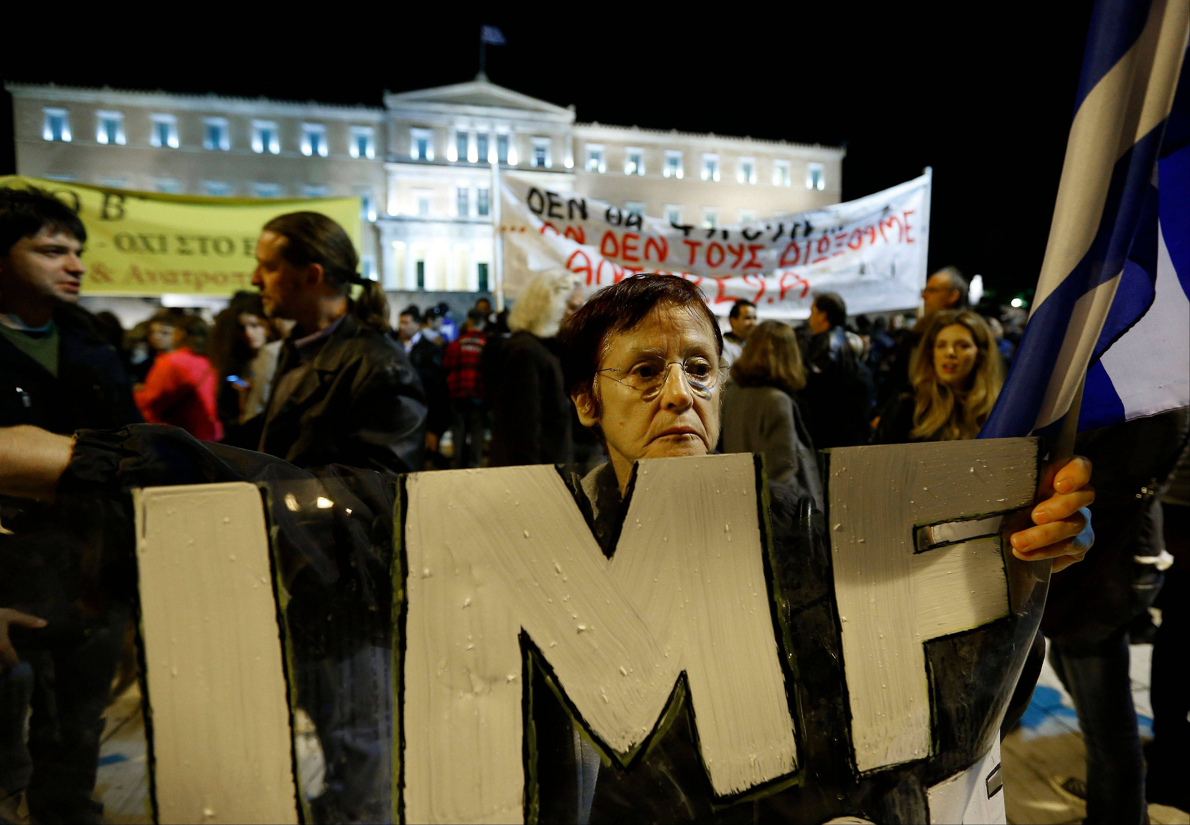 A woman holds an IMF banner in front of the Parliament in Athens on Sunday. Hundreds of protesters were converging on the Greek capital�s main square outside Parliament on Sunday evening, as lawmakers debated the 2013 budget.