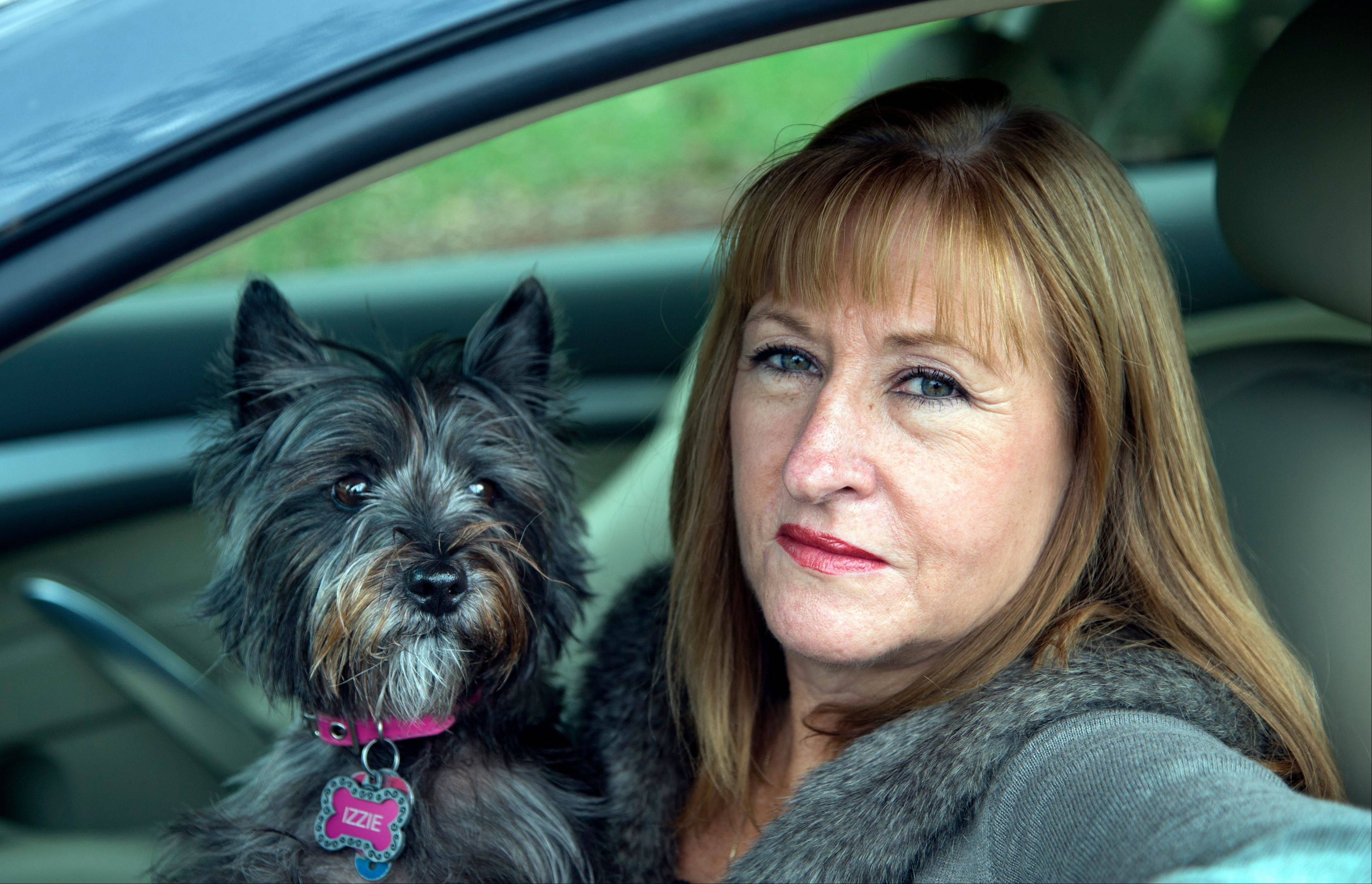 "In this photo taken Nov. 2, 2012, Diane Spitaliere and her pet dog Izzie sit in her car outside her house in Alexandria. Baby boomers, that giant population bubble born between 1946 and 1964, started driving at a young age and became more mobile than any generation before or since. Spitaliere, a 58-year-old who recently retired after working 38 years at the Federal Aviation Administration, said the idea of moving to a retirement or assisted living community ""is just very unappealing to me."""