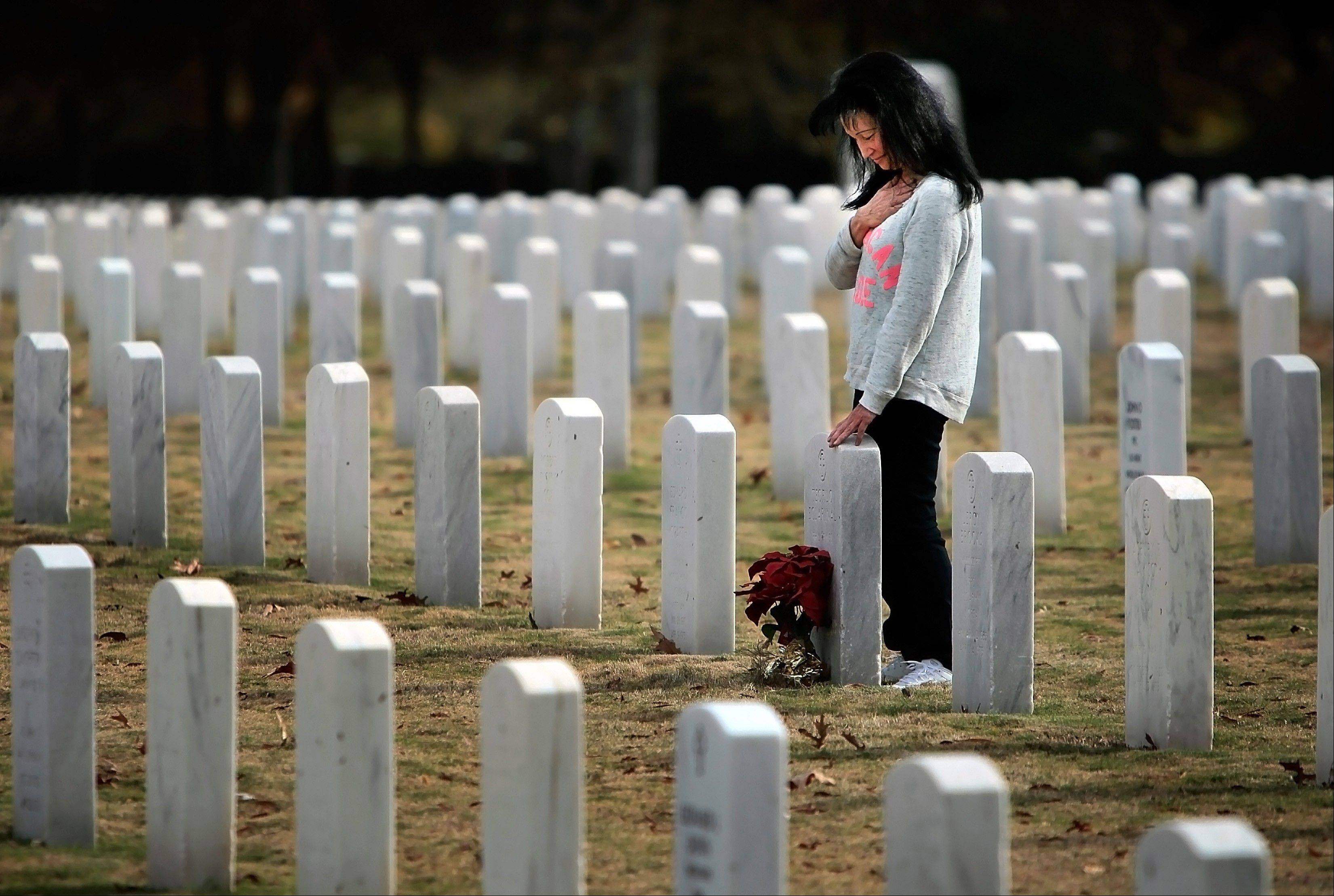 As a band nearby plays the National Anthem, Priscilla Eclarinal pays her respects to her father's grave at the annual Veterans Day ceremony at Memphis National Cemetery in Memphis, Tenn., Sunday. Her father, Chief Petty Officer Teofilo Eclarinal, served for 30 years in the U.S. Navy fighting in both World War II and Korea.