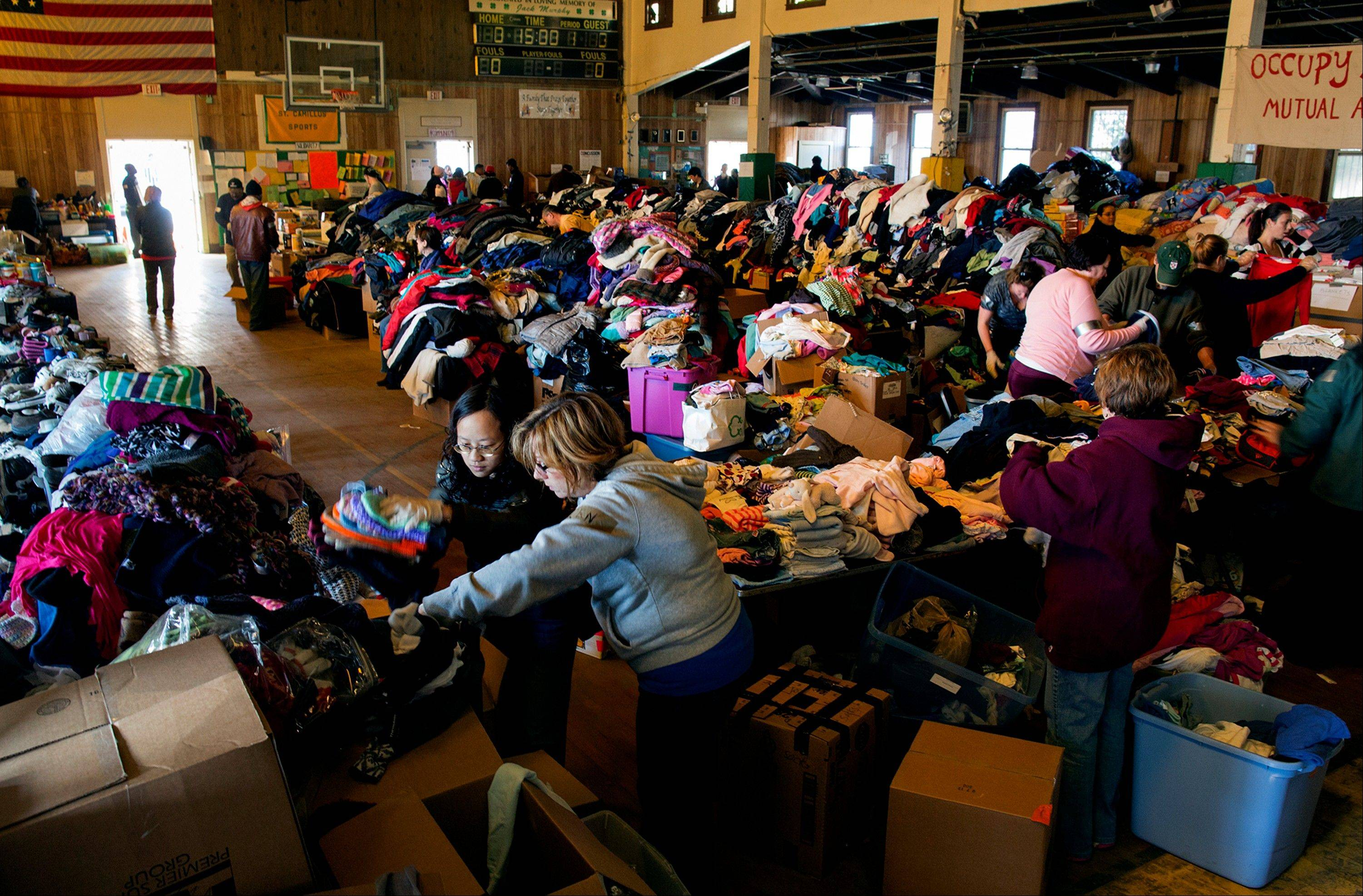 Thousands of food and clothing items are organized by Occupy Sandy volunteers in the school gymnasium at the St. Camillus Roman Catholic Church in the Rockaway Park neighborhood of the borough of Queens, New York, Sunday, almost two weeks in the wake of Superstorm Sandy.