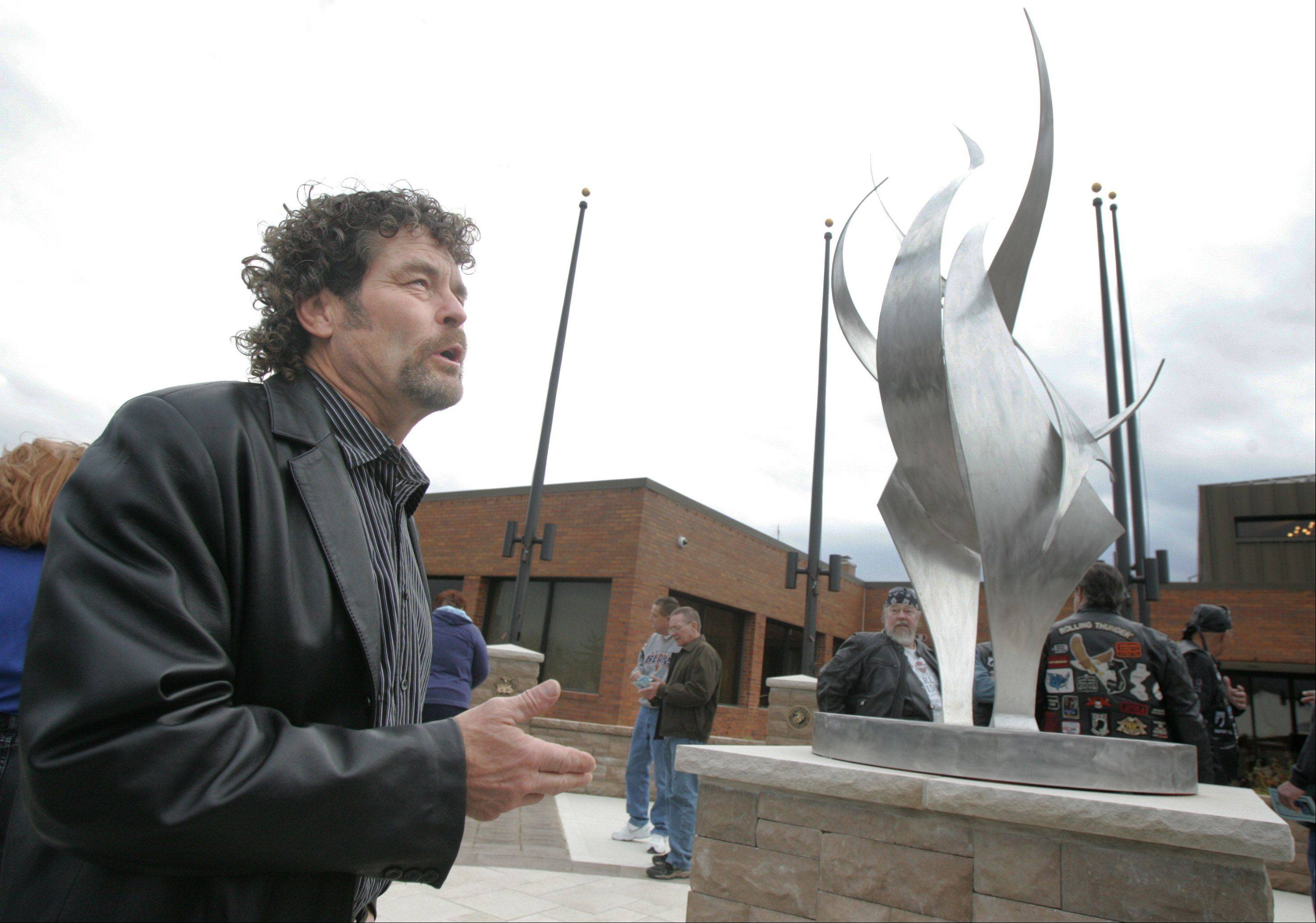 "Artist Bruce Niemi talks about his sculpture called ""Always Remembered"" before the Veterans Day ceremony Sunday at the Hanover Park Village Hall featuring the unveiling of Veterans Memorial Plaza. The dedication was hosted by VFW Post 11018 and Post 5151 and the Village of Hanover Park."