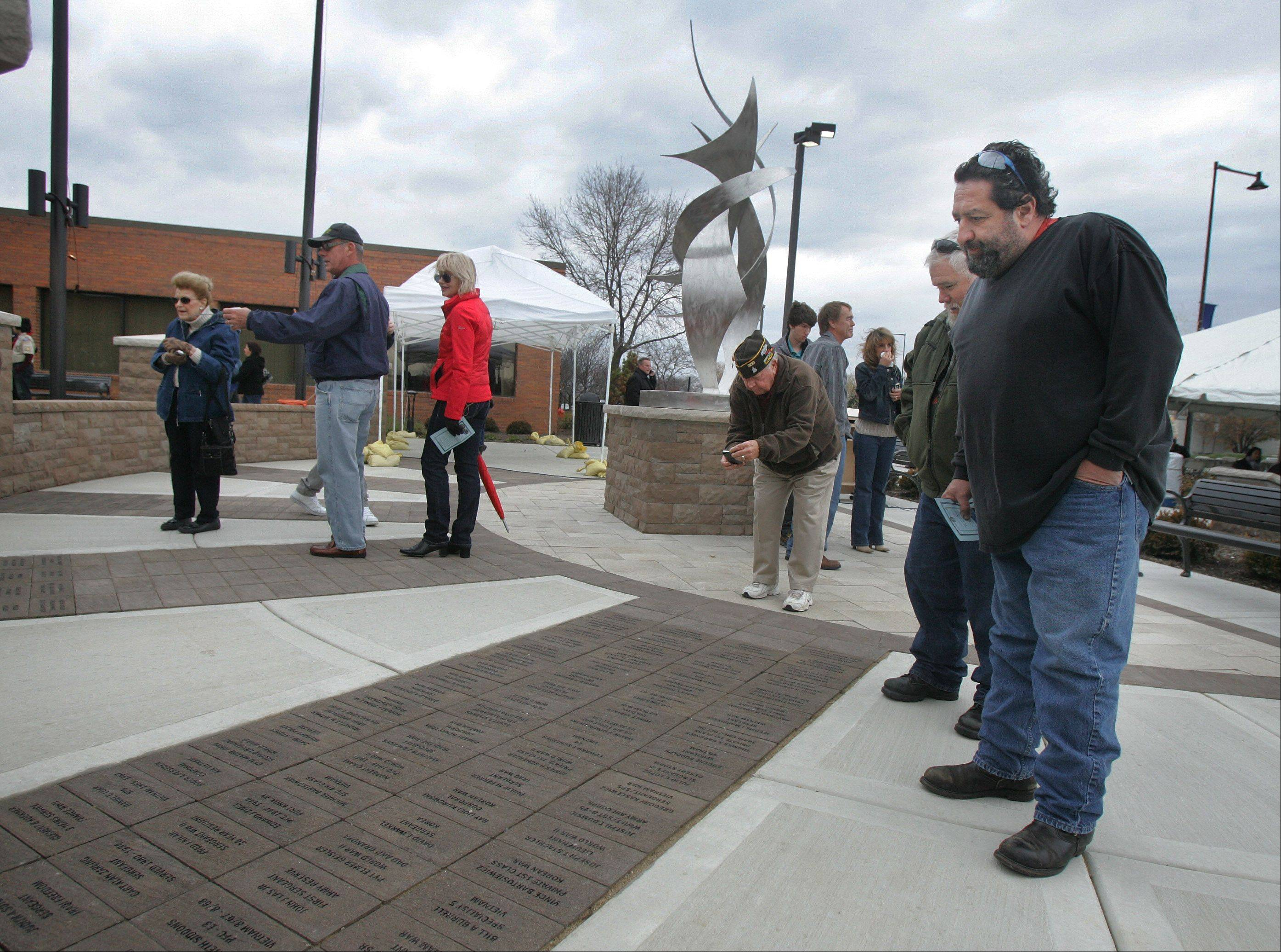 Frank Zepeda, of Hanover Park, right, looks for the name of his great uncle William Bufalini before the Veterans Day ceremony Sunday at the Hanover Park Village Hall featuring the unveiling of Veterans Memorial Plaza. Bufalini was a World War II veteran who was at Pearl Harbor when it was attacked by Japan.