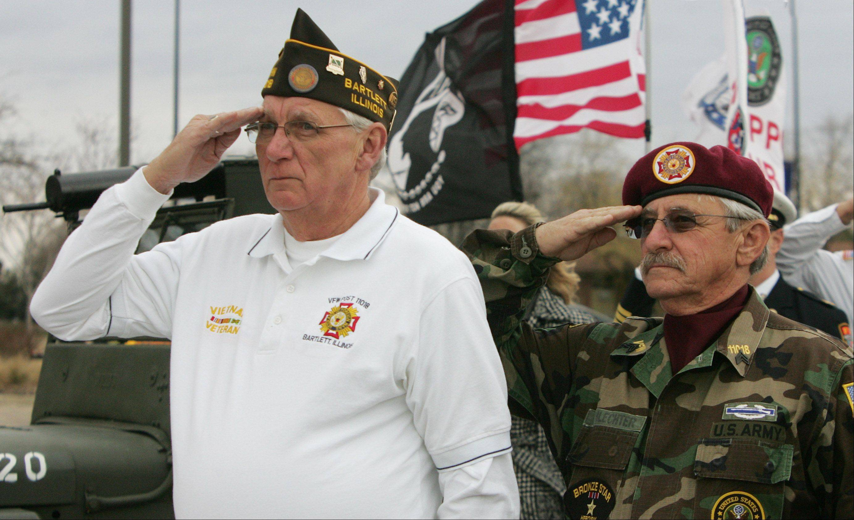 Veterans Joe Tremmel, left, and Glen Schlechter salute as the national anthem is sung during the Veterans Day ceremony Sunday at the Hanover Park Village Hall featuring the unveiling of Veterans Memorial Plaza. The dedication was hosted by VFW Post 11018 and Post 5151 and the Village of Hanover Park.