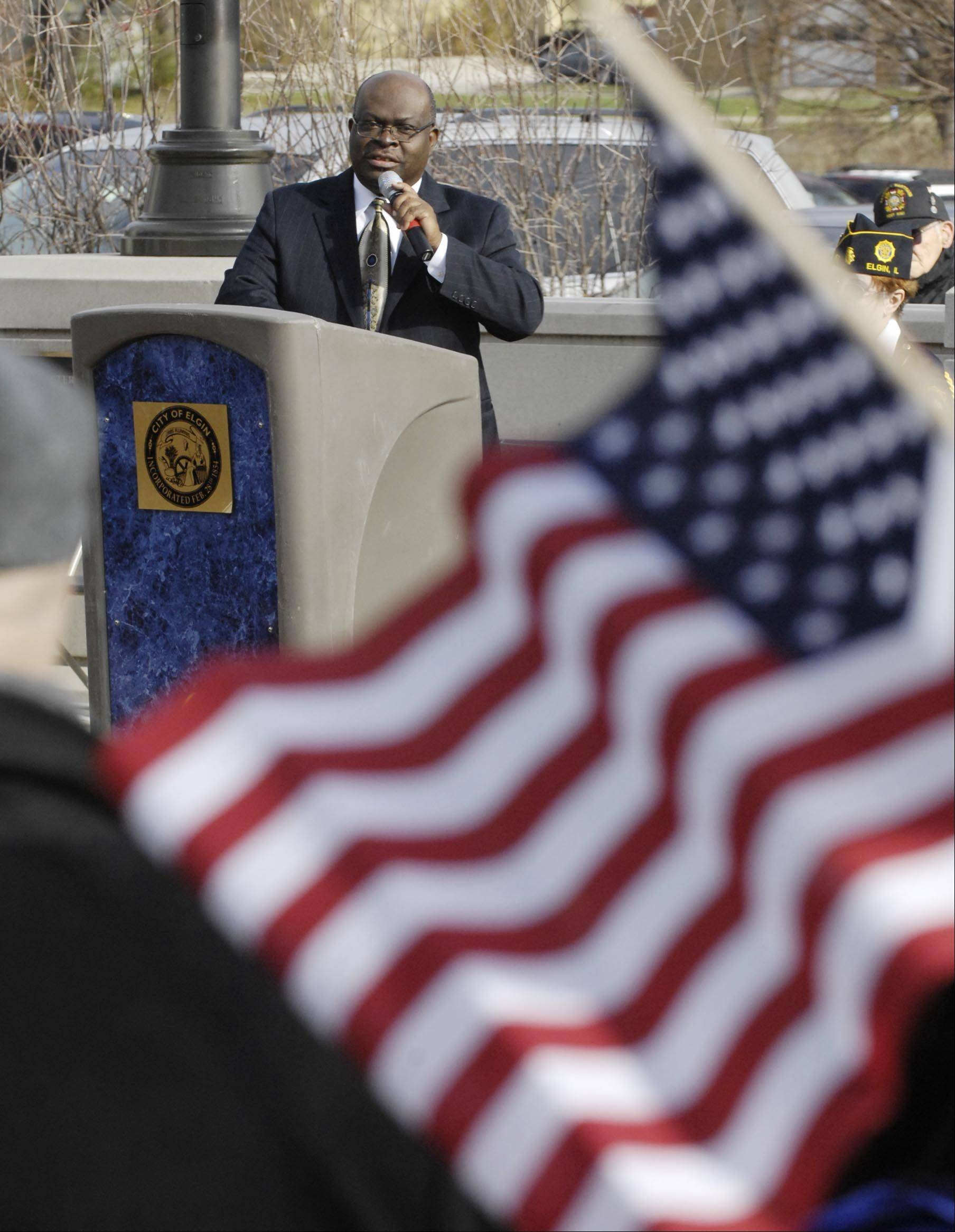 David Sam, Elgin Community College President, speaks Sunday at a Veterans Day ceremony at the waterfront memorial behind the Gail Borden Library in Elgin. The official groundbreaking for Phase II of the memorial also took place.