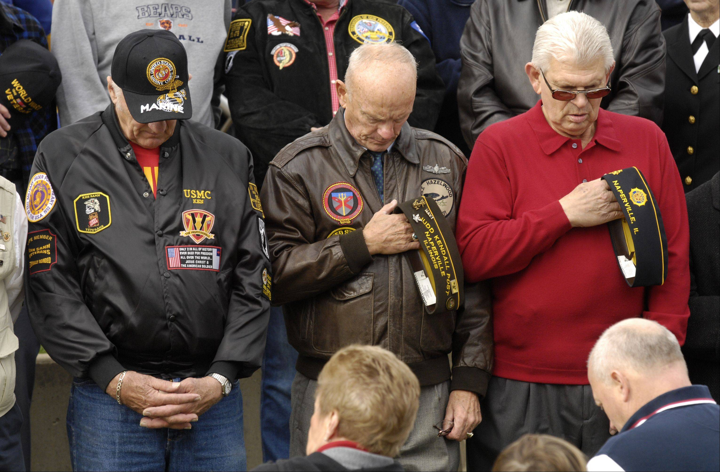 Veterans bow their head during the Naperville Veterans Day Ceremony, Sunday.