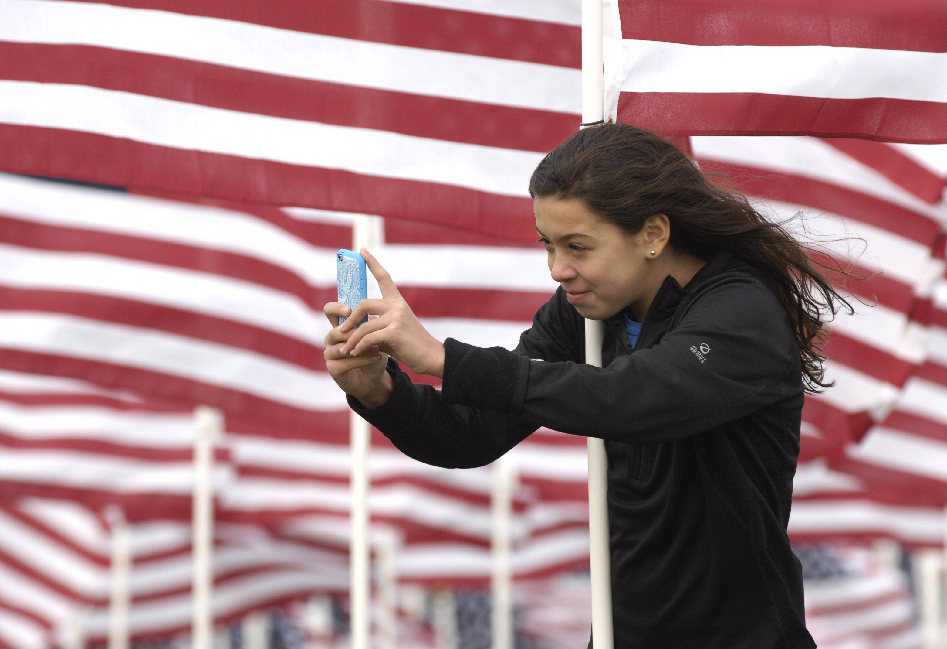 Alexis Davila, 12 of Naperville braces herself against a flagpole as she photographs the Naperville Healing Field on Rotary Hill, Sunday.