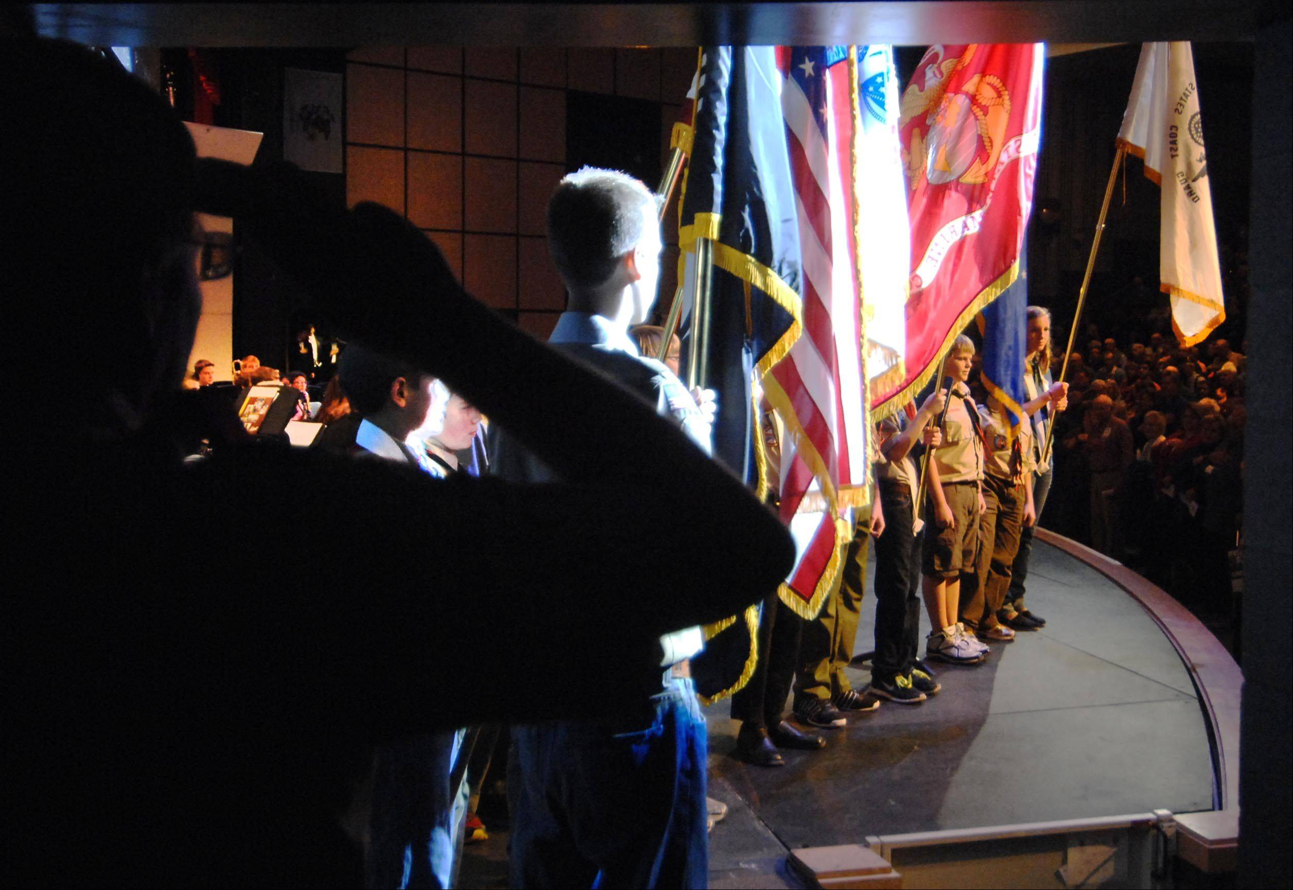 Scouts from St. Charles Girl Scout Troop #1036, Boy Scout Troo #56, and Elburn boy Scout Troop #7 stand at attention as they present the colors Sunday at the Sixth Annual Veterans Celebration Concert for Veterans Day at St. Charles North High School.