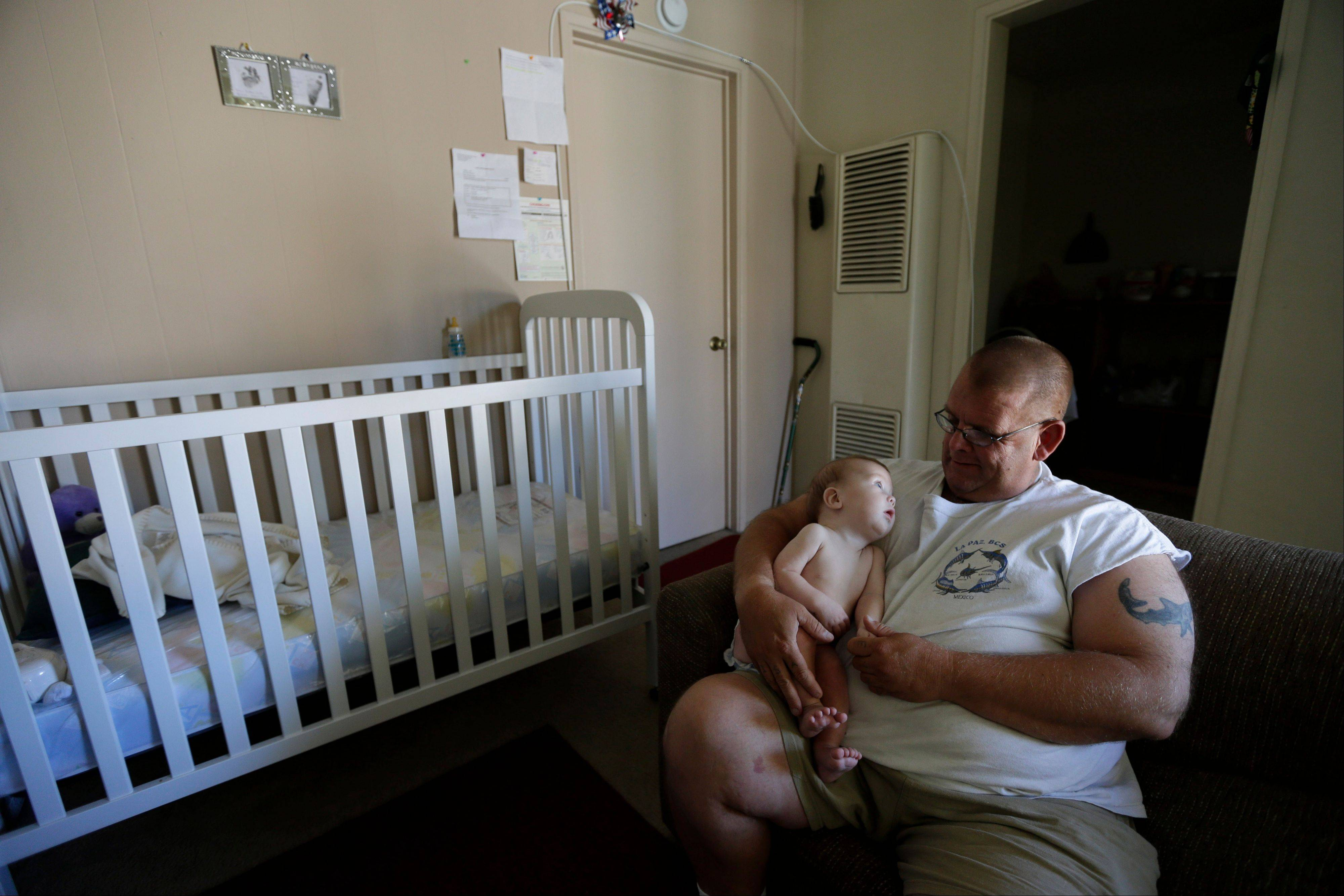 In this Oct. 9, 2012 picture, veteran Arthur Lute holds his is 5-month-old son Evan in his one-bedroom apartment in Chula Vista, Calif. Lute's arduous journey from his days as a U.S. Marine to his nights sleeping on the streets illustrates the challenge the Obama administration faces to make good on its audacious promise: End homelessness among veterans by 2015.
