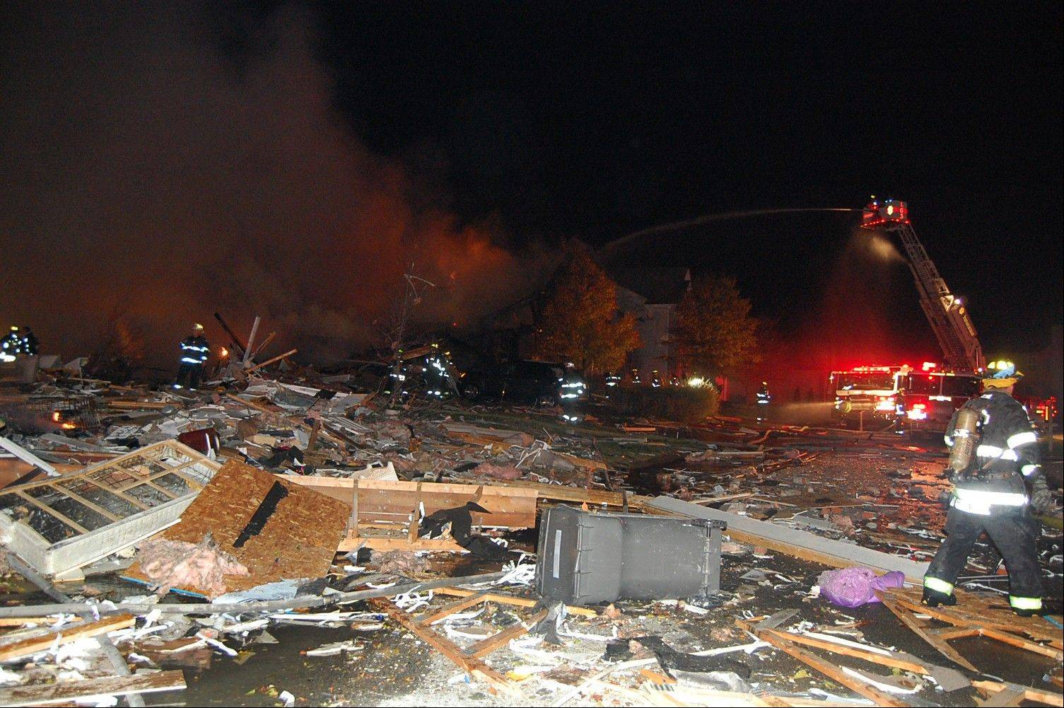 In this photo provided by the Indianapolis Fire Department, firefighters work the scene where an explosion and fire has killed two people and damaged more than a dozen homes late Saturday and early Sunday, Nov. 11, 2012, in the Richmond Hill subdivision in Indianapolis.