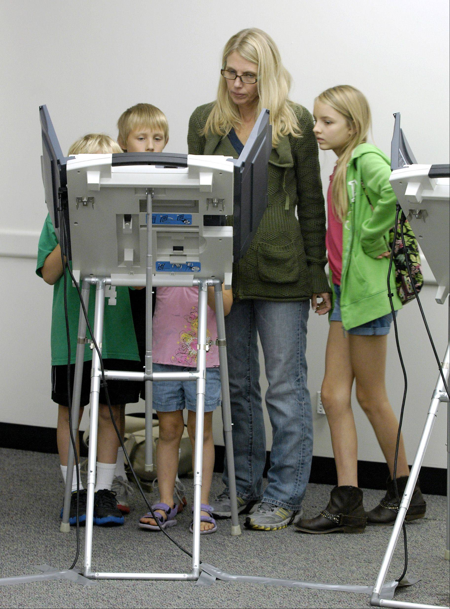 Laura Penosky of Wheaton, with some of her children looking on, took advantage of the first day of early voting by casting her ballot Oct. 22 at the DuPage County government building in Wheaton. Penosky's daughter, Lydia Penosky, 21, voted for the first time at an adjoining booth.