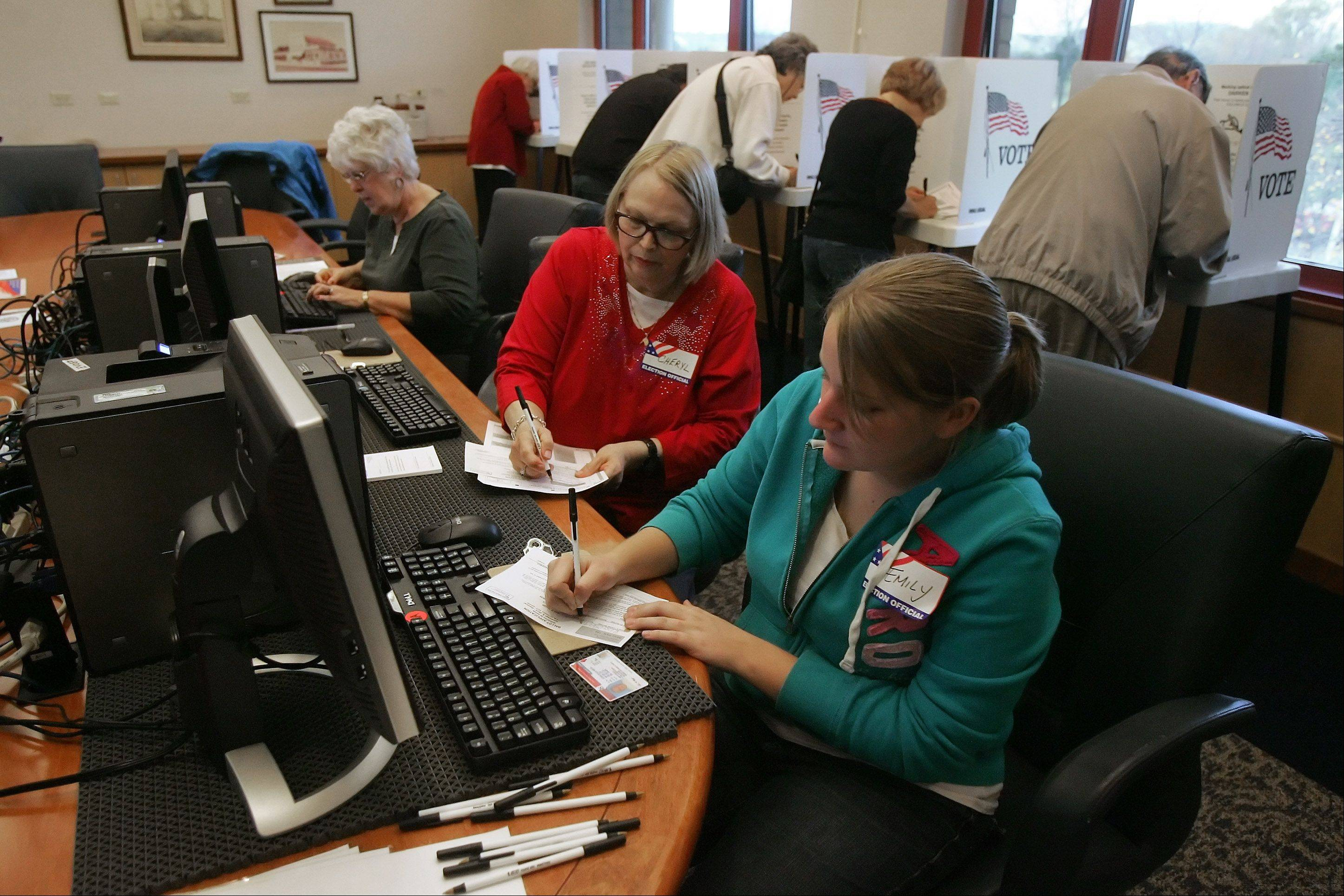 Election judges Emily Dewitt, front, Cheryl Bradford and Lois Caslavka are busy helping voters get their ballots on the first day of early voting Oct. 22 at Fremont Public Library in Mundelein. There was a long line of people waiting to vote.