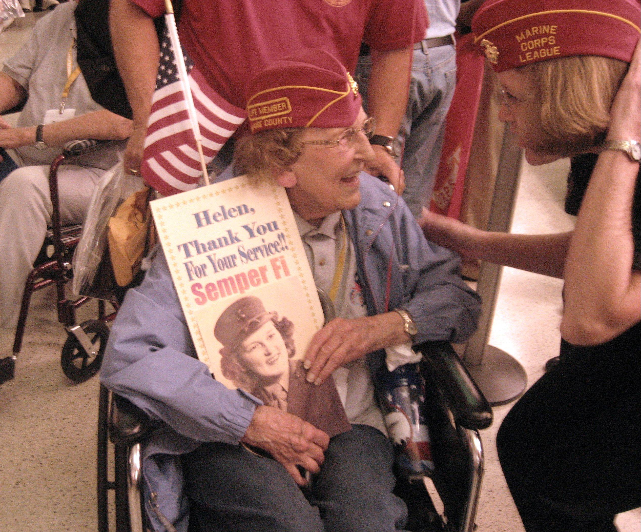 Clutching a poster featuring her likeness from her days as a Marine Corps airplane mechanic, Helen Ehlers, 89, of Wheaton, soaks in the adoration from a fellow DuPage County Marine Corps League member welcoming her home from an Honor Flight trip to Washington, D.C., to see the World War II Memorial.
