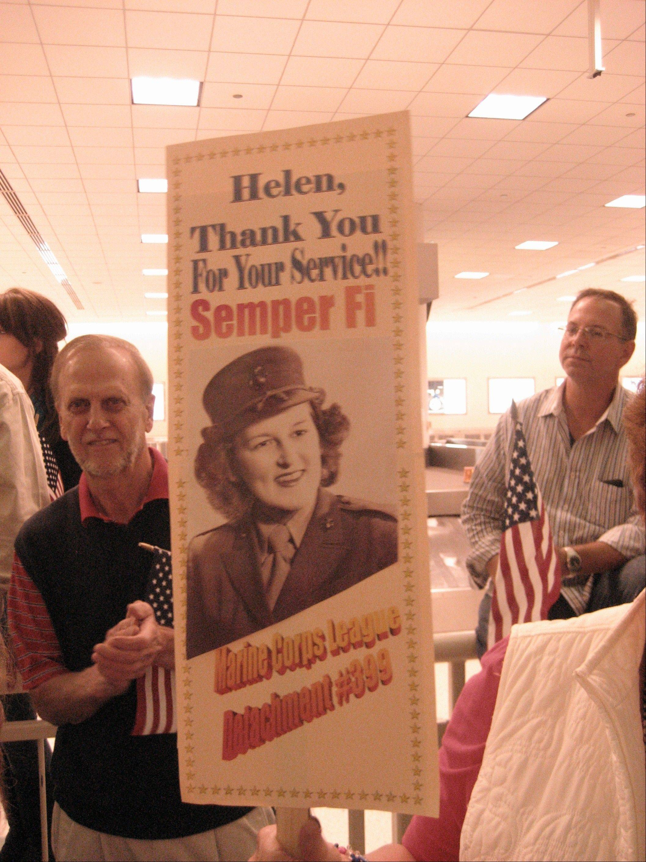 This poster features a photo of Wheaton resident Helen Ehlers, now 89, taken during her service as a Marine Corps airplane mechanic. Honor Flight volunteers welcoming veterans home after a trip to the World War II Memorial go beyond the call to show their gratitude.