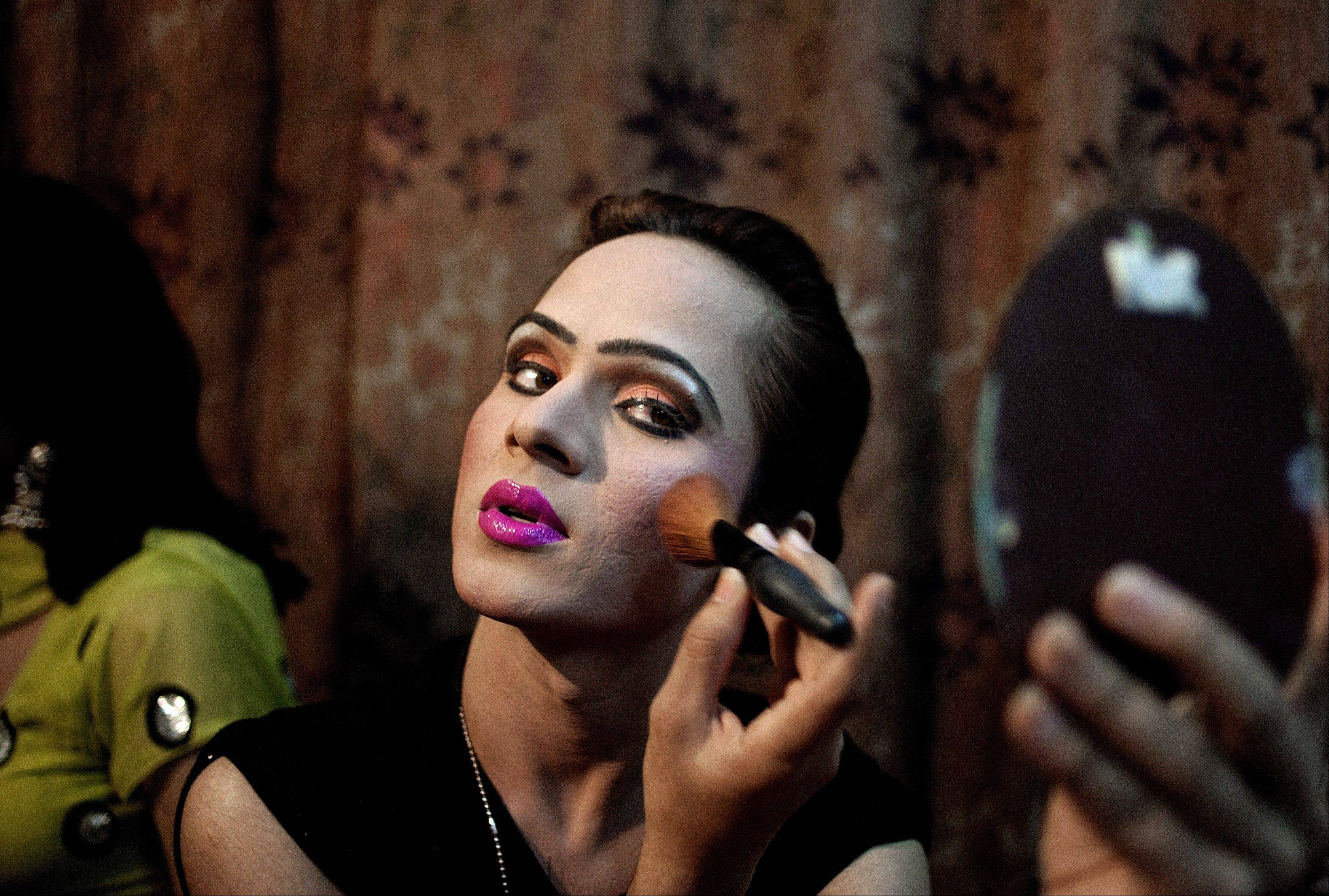 Kate Heart, 19, a Pakistani transgender, applies makeup before heading to a wedding party where she will perform. Transgender people live in a tenuous position in conservative Pakistan, where the roles of the sexes are traditionally starkly drawn. One role where they are tolerated is as dancers at weddings and other celebrations at which men and women are strictly segregated.