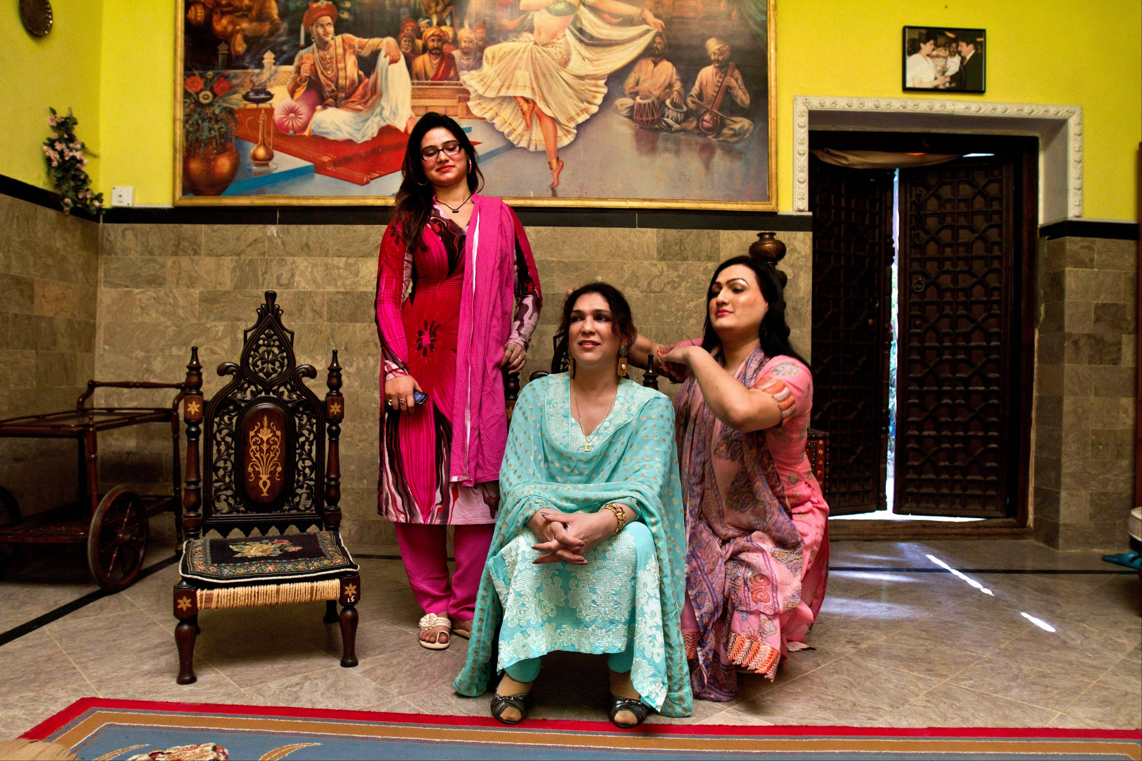 Pakistani transgender women Sonia, right, and Mahim, left, chat with their community head Almas Bobby, 42, center, at Almas' home in Rawalpindi, Pakistan.