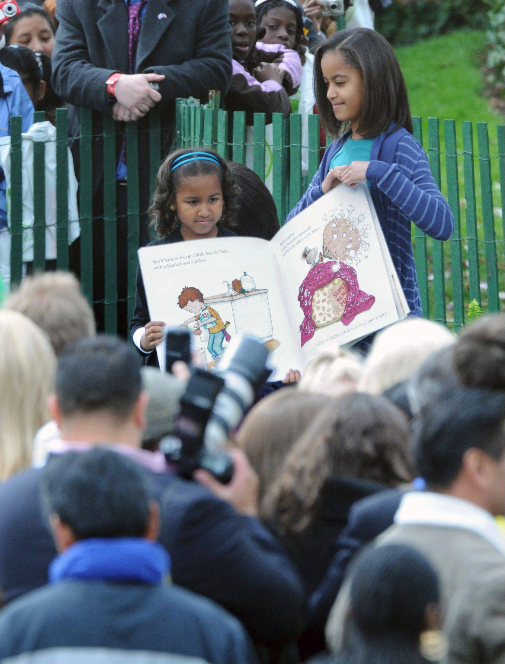 President Barack Obama and family host thousands of kids of all ages for an annual Easter Egg Roll at the White House in 2009. Pictured, Sasha, left, and Malia Obama read to a group gathered on the South Lawn.