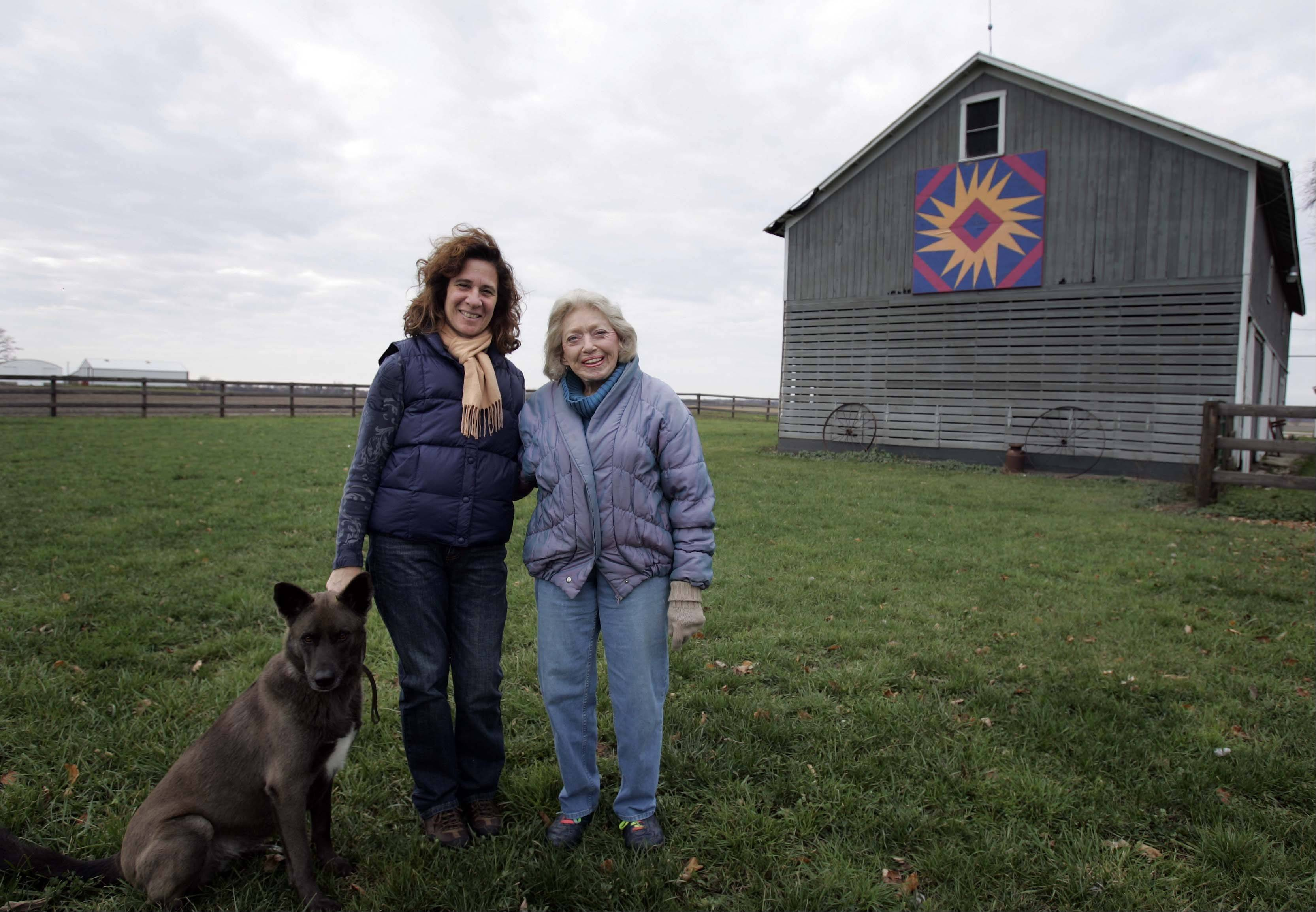 Angela Beestra, left, with Nancy Wicker of Harvard, who together installed the quilted barn panel on Beestra's Harvard farm. Beestra's dog Lilly is also pictured.