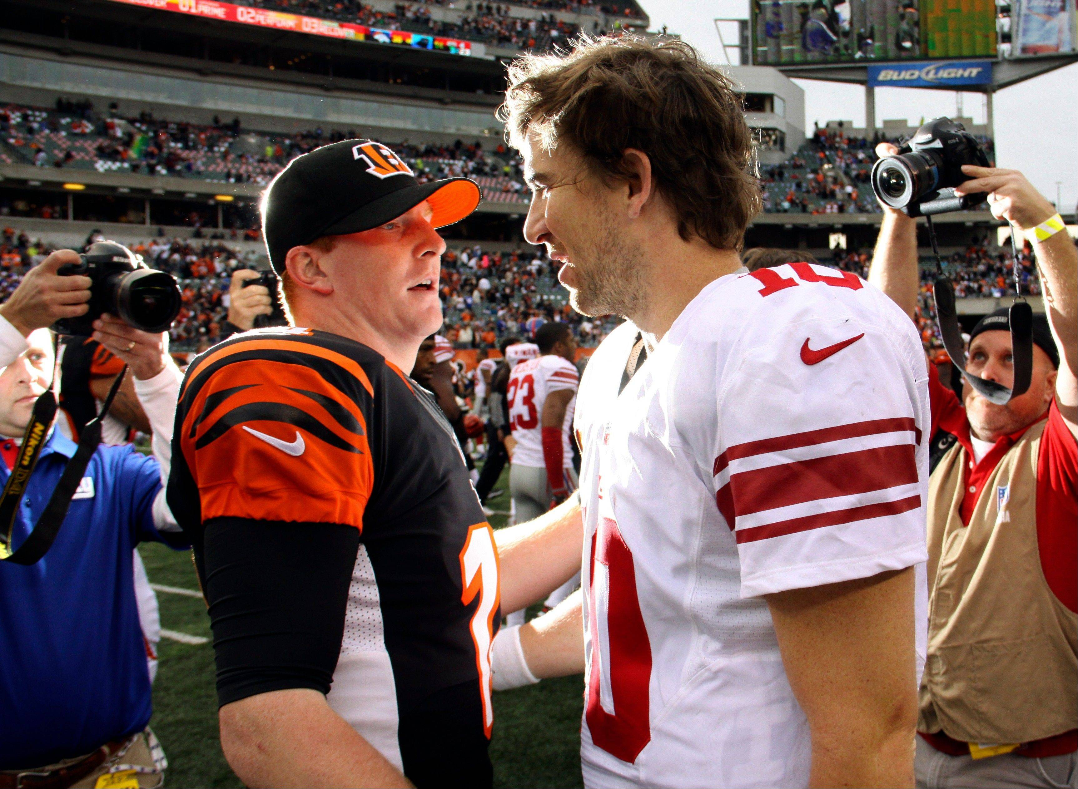 Cincinnati Bengals quarterback Andy Dalton (14) meets with New York Giants quarterback Eli Manning (10) after the Bengals' 31-13 win in an NFL football game, Sunday, Nov. 11, 2012, in Cincinnati.