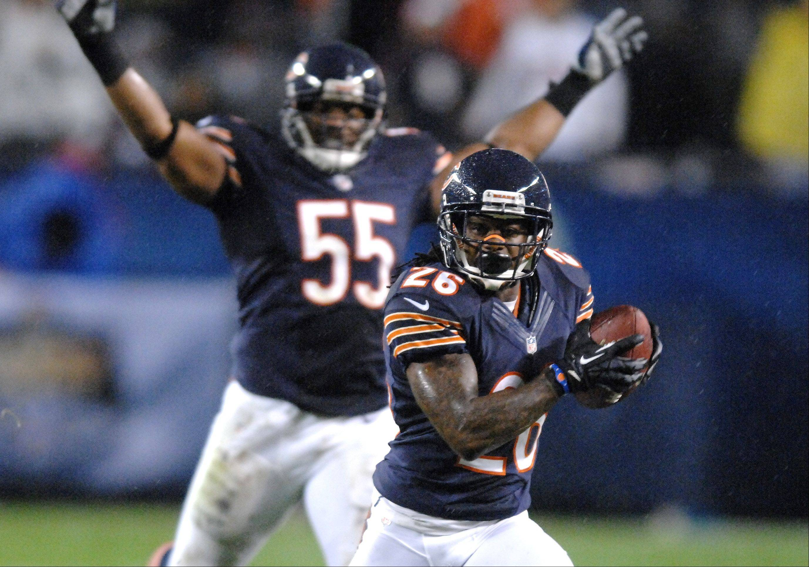 Chicago Bears outside linebacker Lance Briggs (55) celebrates in the background as Tim Jennings returns his first quarter interception deep into Texas territory.