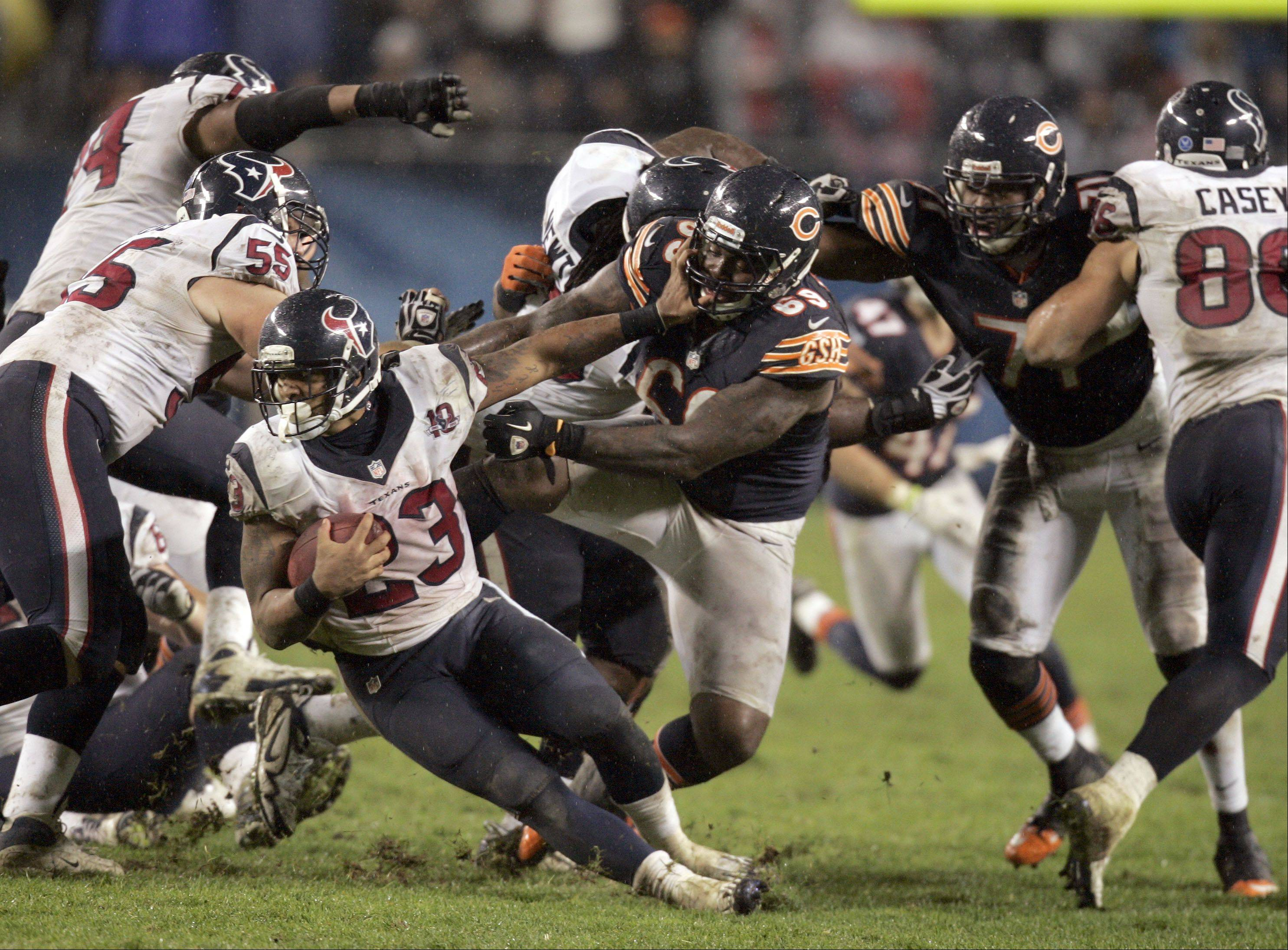 Houston Texans running back Arian Foster (23) tries to make ground up as Chicago Bears defensive tackle Henry Melton (69) brings the hurt during the game Sunday November 11, 2012 at Soldier Field in Chicago.