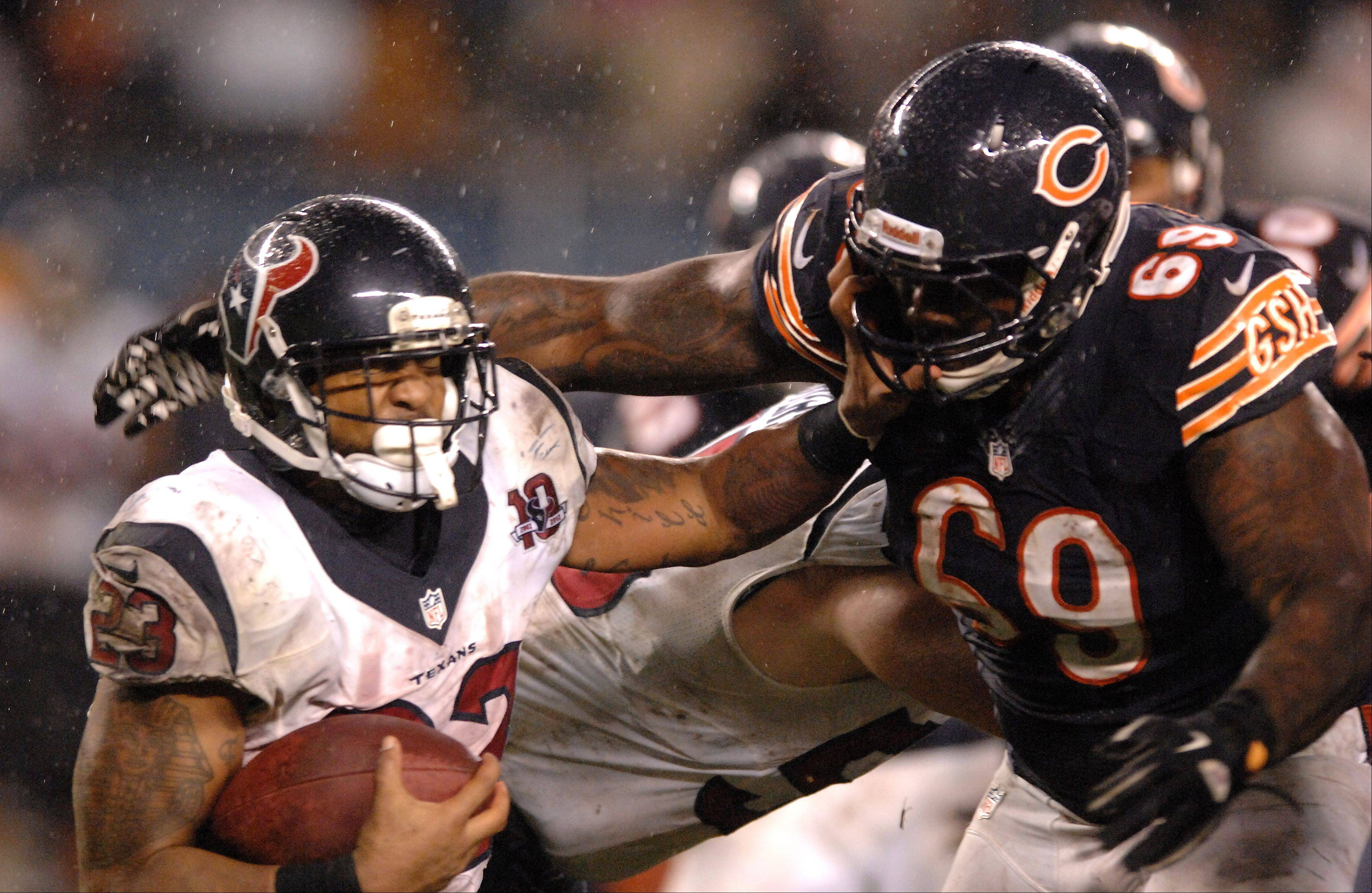 Houston Texans running back Arian Foster (23) is brought down for a loss by Chicago Bears defensive tackle Henry Melton (69) during Sunday's game.