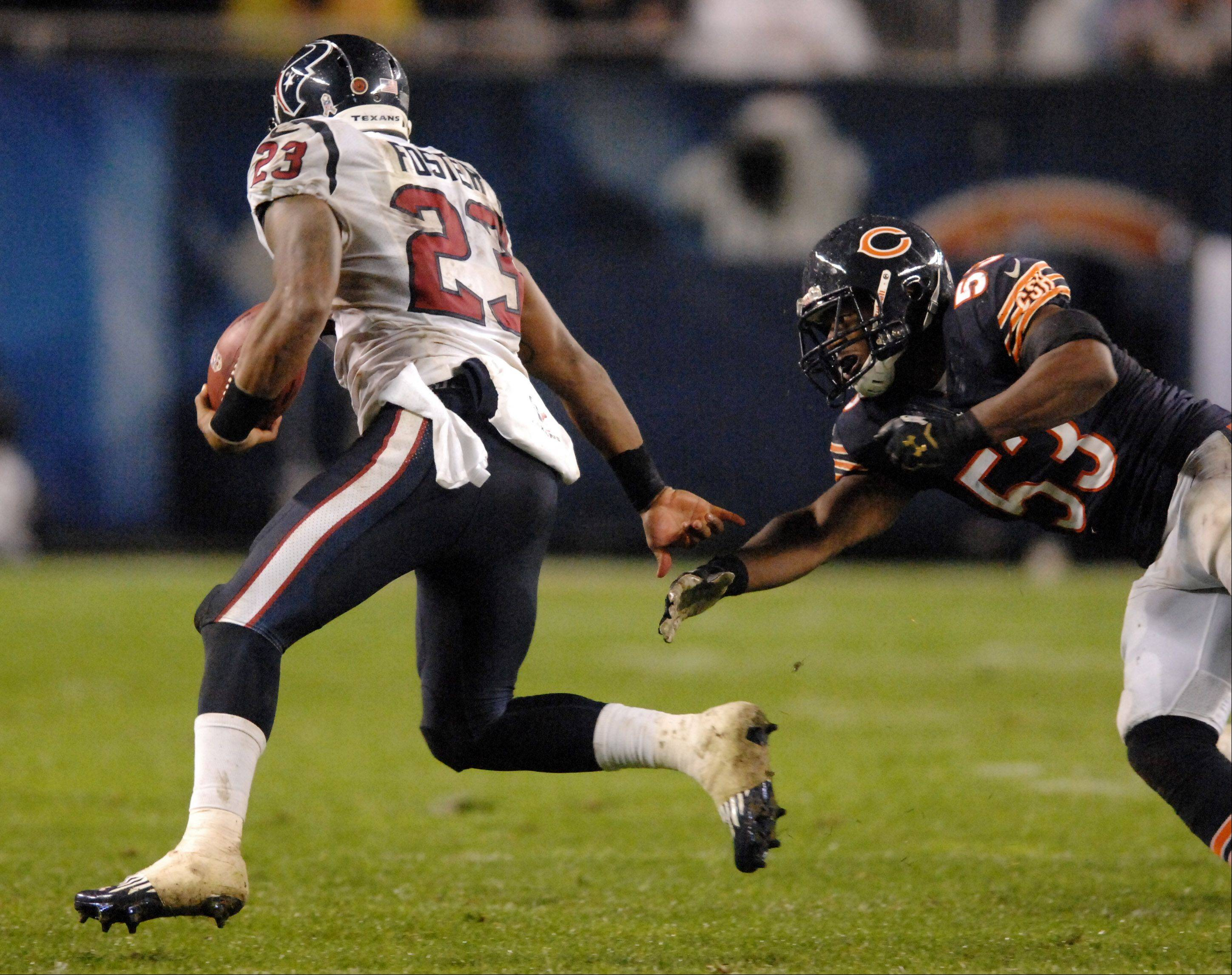 Houston Texans running back Arian Foster (23) shrugs aside an attempted tackle by Chicago Bears outside linebacker Nick Roach (53) for a big second quarter gain during Sunday's game at Soldier Field in Chicago.