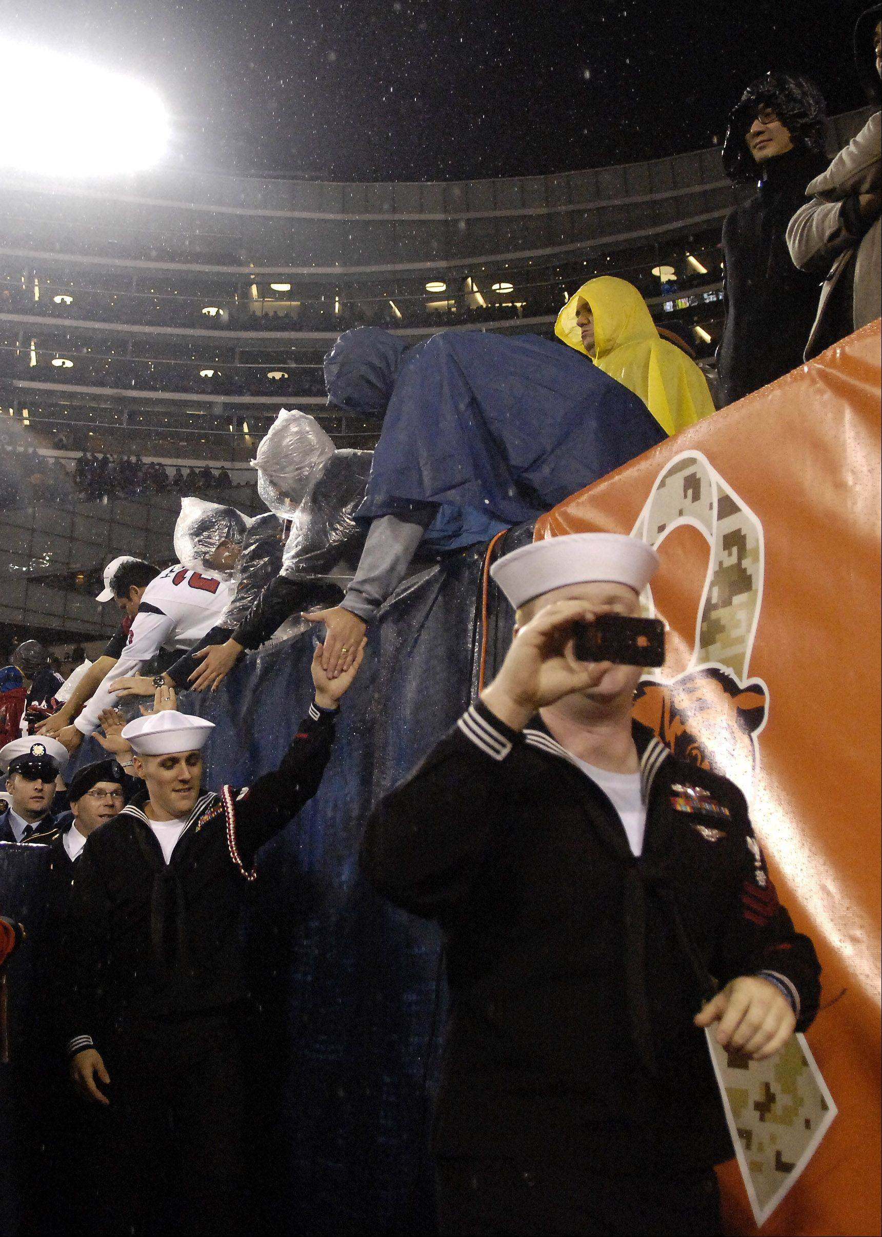 Members of the military give high fives to the fans during Sunday's game at Soldier Field in Chicago.